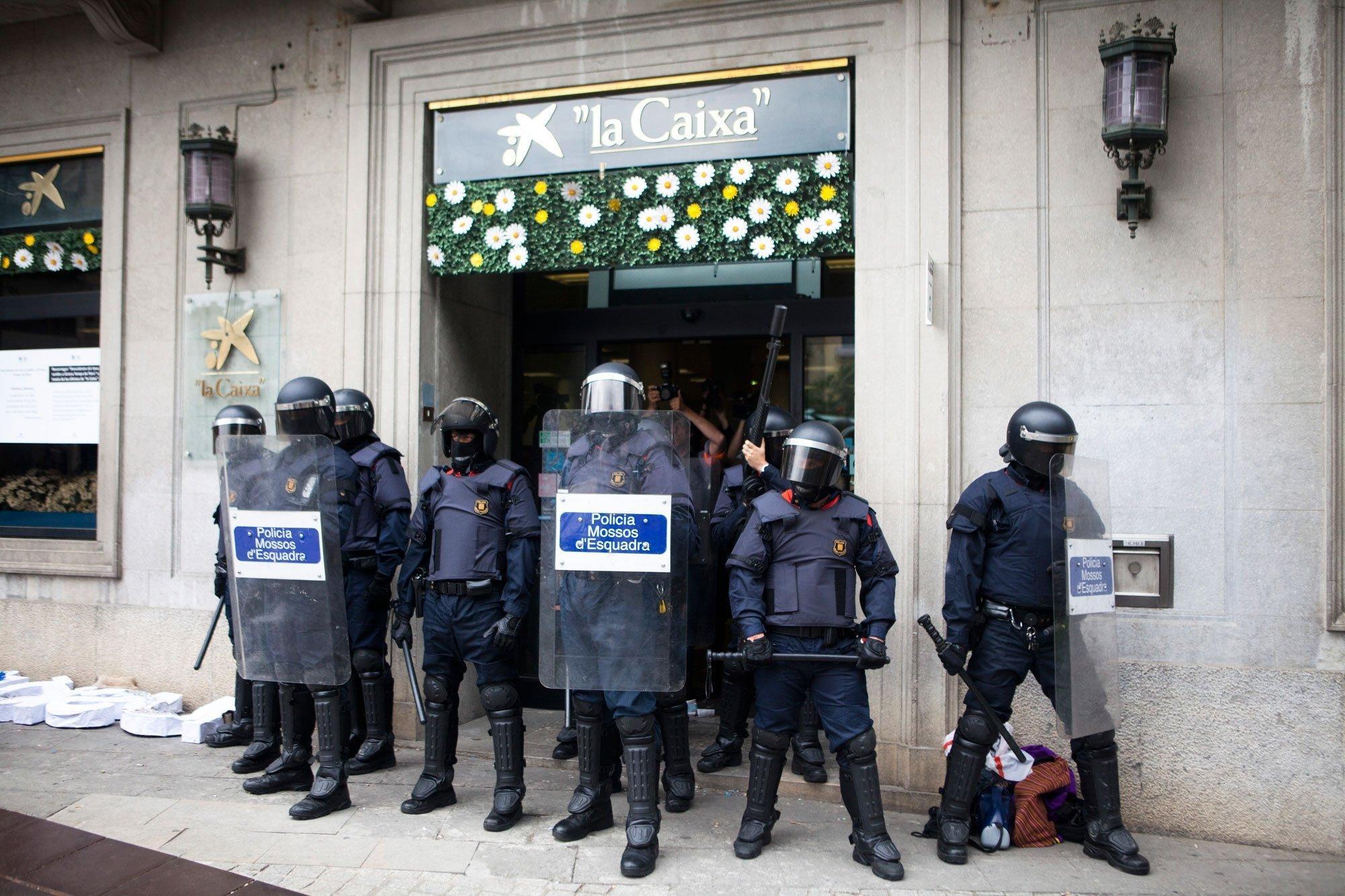 In Katalonien wird eine Bank von schwer bewaffneten Polizisten bewacht.