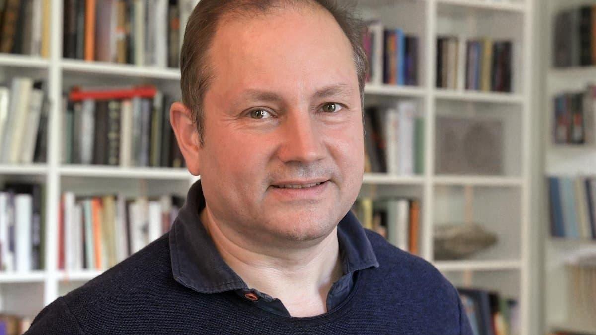 Portrait-Aufnahme von Christian Schwägerl vor einem Bücherregal.