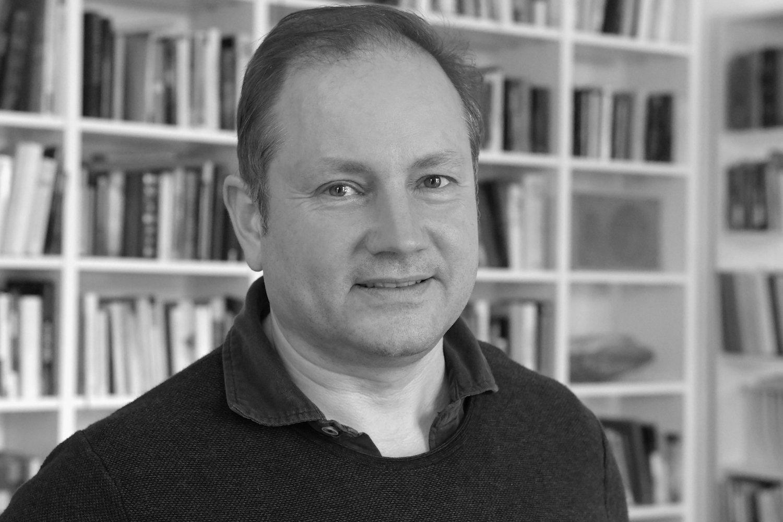 Portrait-Aufnahme von Christian Schwägerl vor einem Bücherregal in schwarz/weiß.