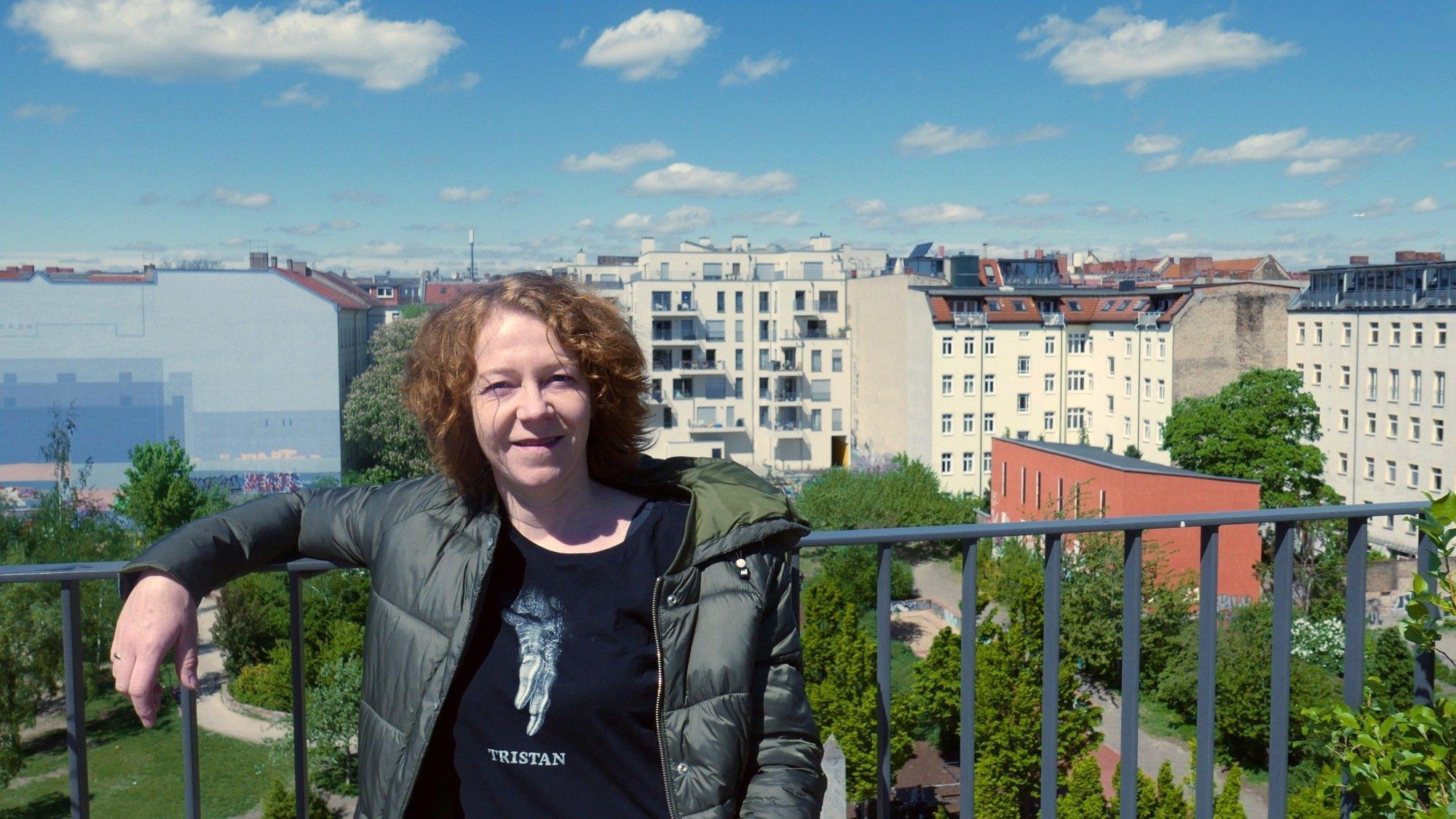 Christiane Habermalz lehnt an einem Geländer. Im Hintergrund sieht man einen Park und mehrstöckige Wohnhäuser.