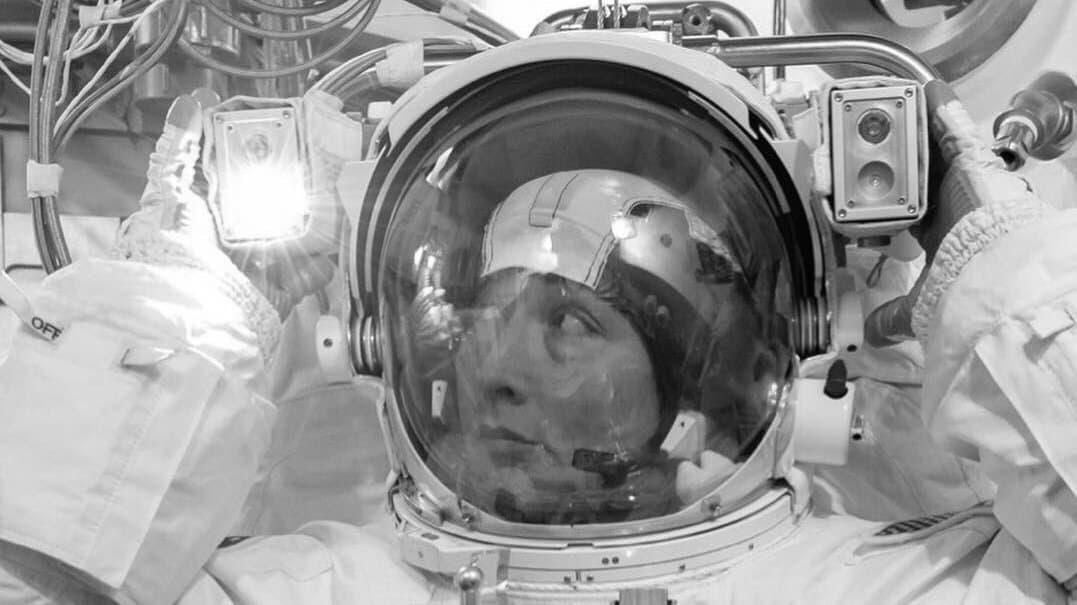 Astronautin im Raumanzug greift an den Helm und blickt nach links oben, wo erst eine der zwei Helmlampen brennen.