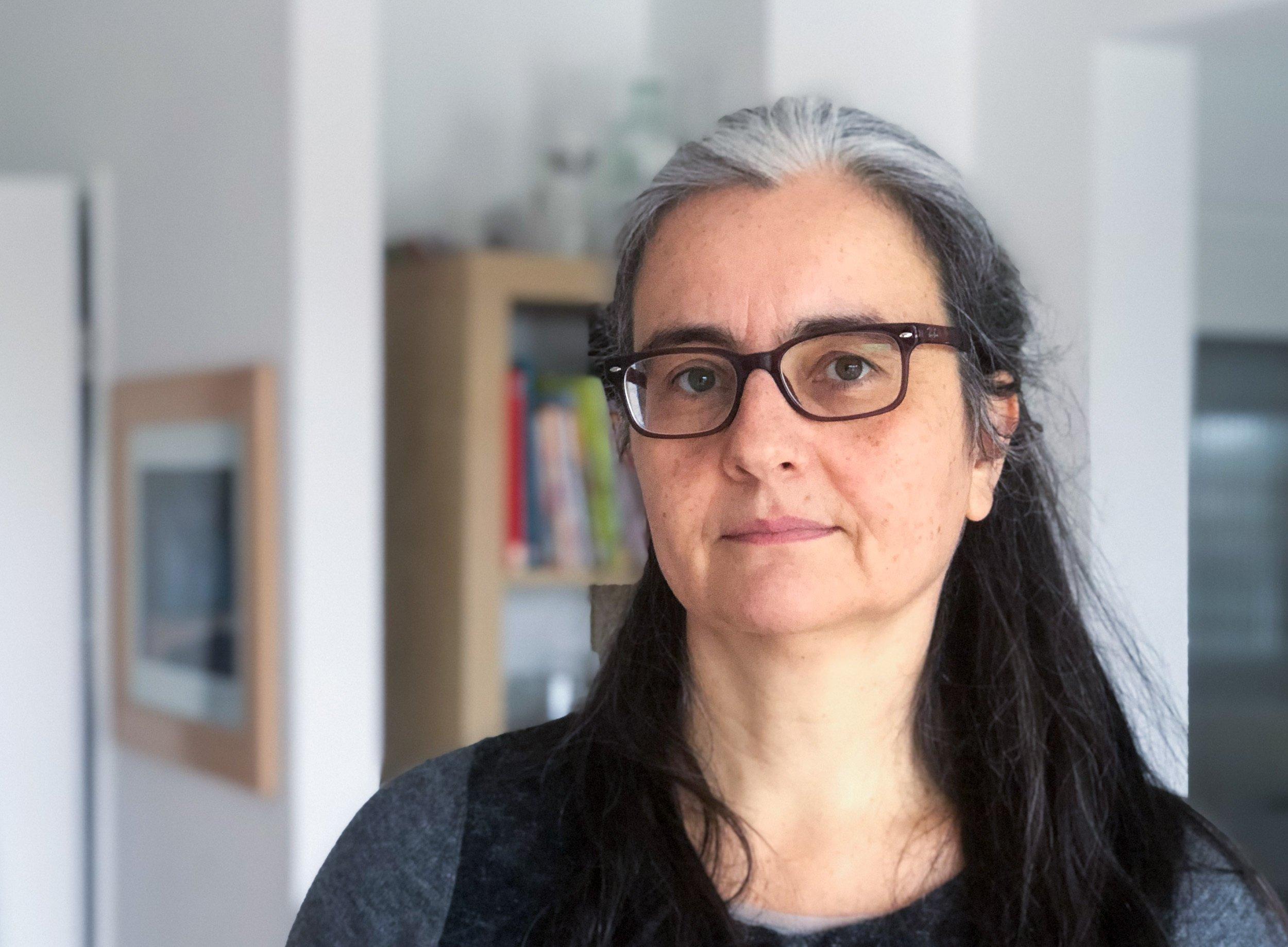Eine Frau mit langen schwarzen Haaren und Brille blickt in die Kamera.