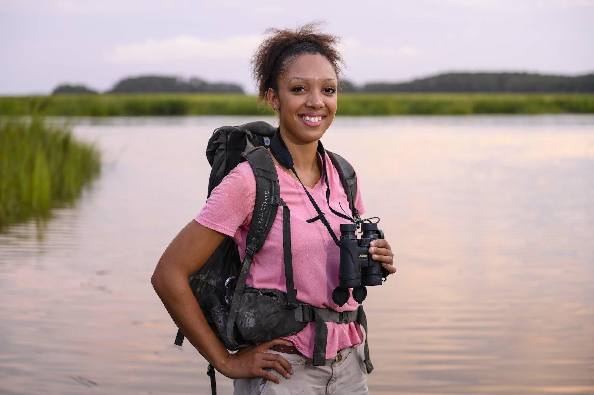 Zu sehen ist Corina Newsome mit einem Fernglas um den Hals in der Natur, vor einem Gewässer.