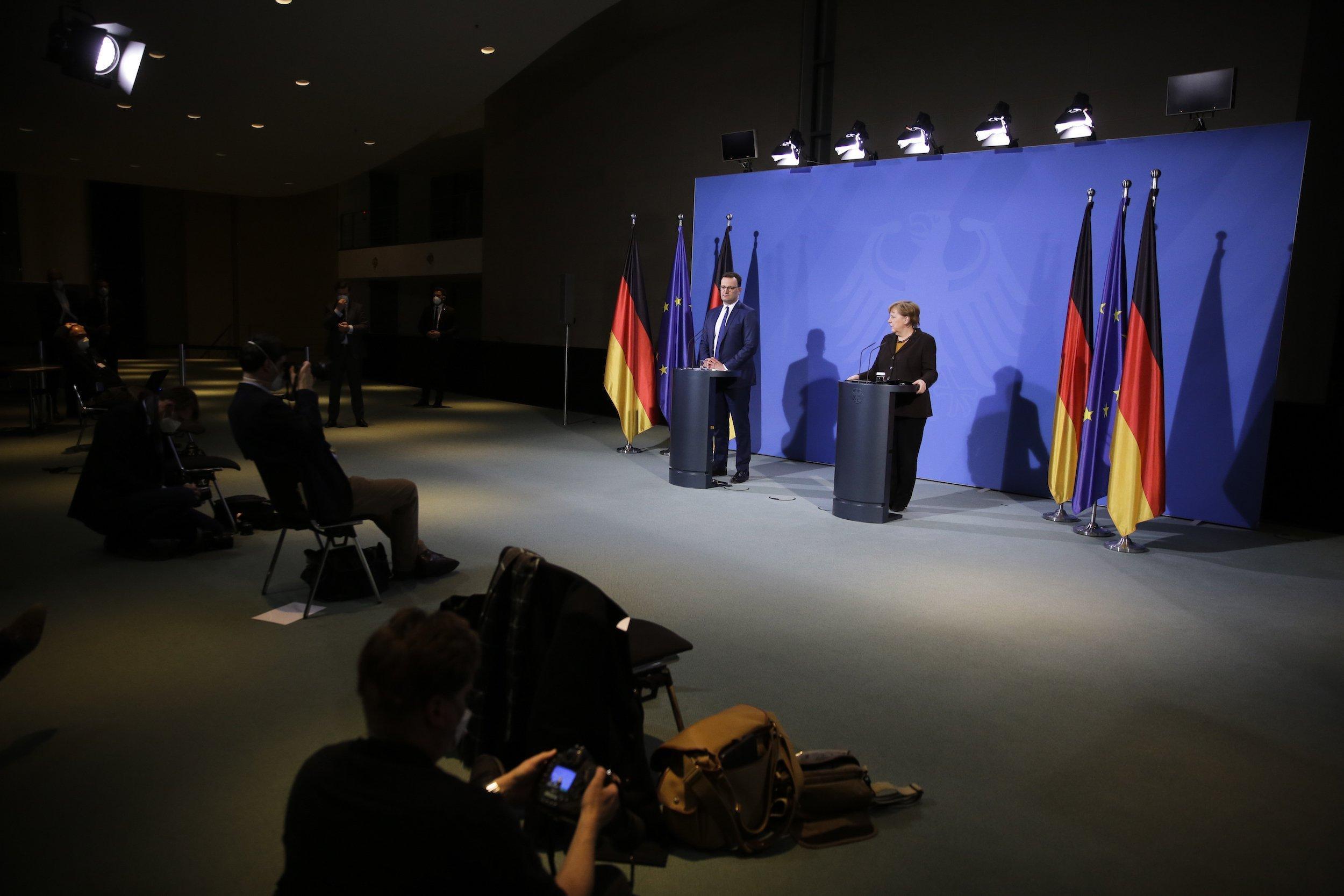 Merkel und Spahn stehen an Redepulten vor blauem Hintergrund, vor ihnen ein leerer Saal mit wenigen Journalistïnnen.