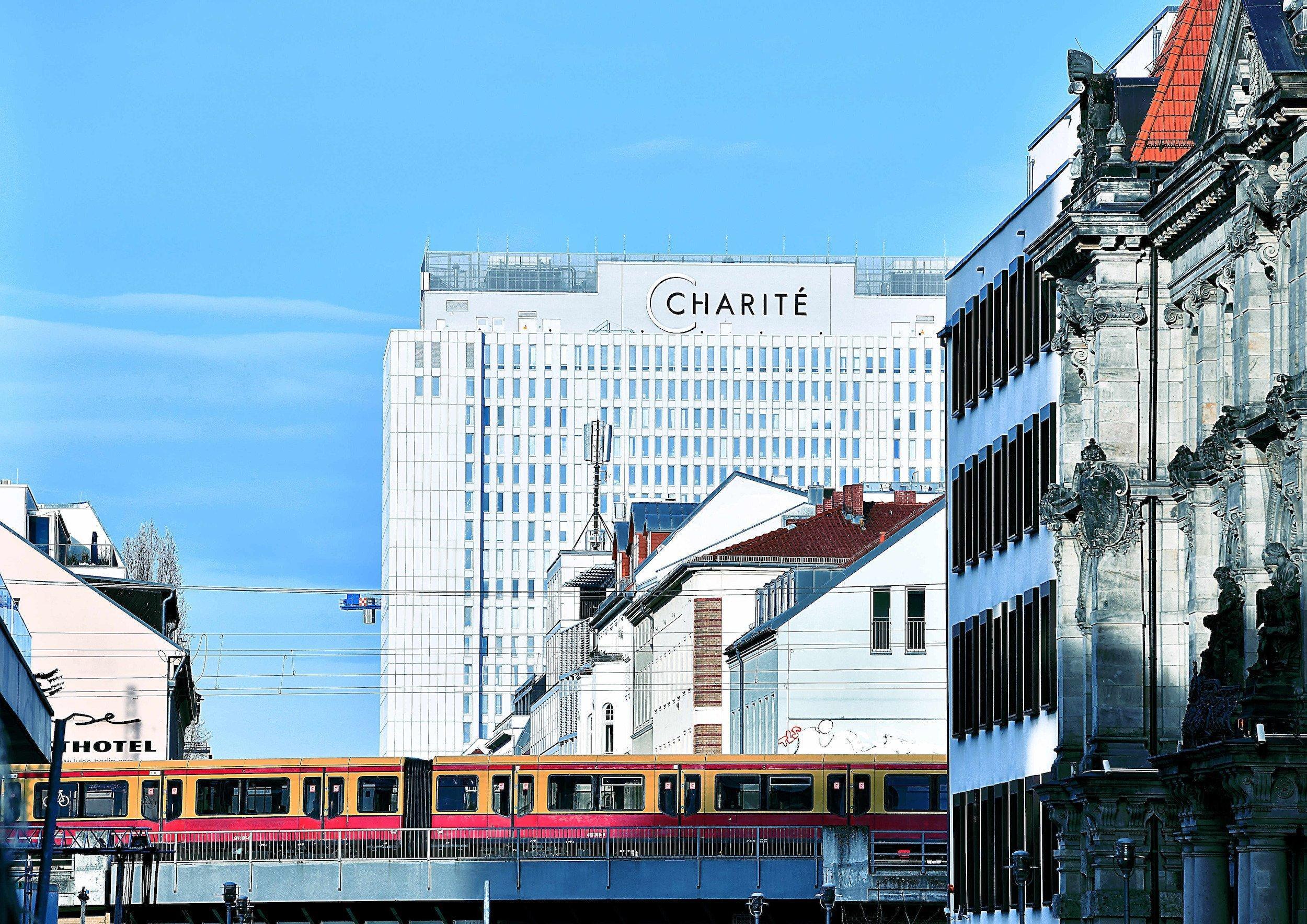 Das Hochhaus der Charité im Berliner Zentrum, im Vordergrund eine S-Bahn.