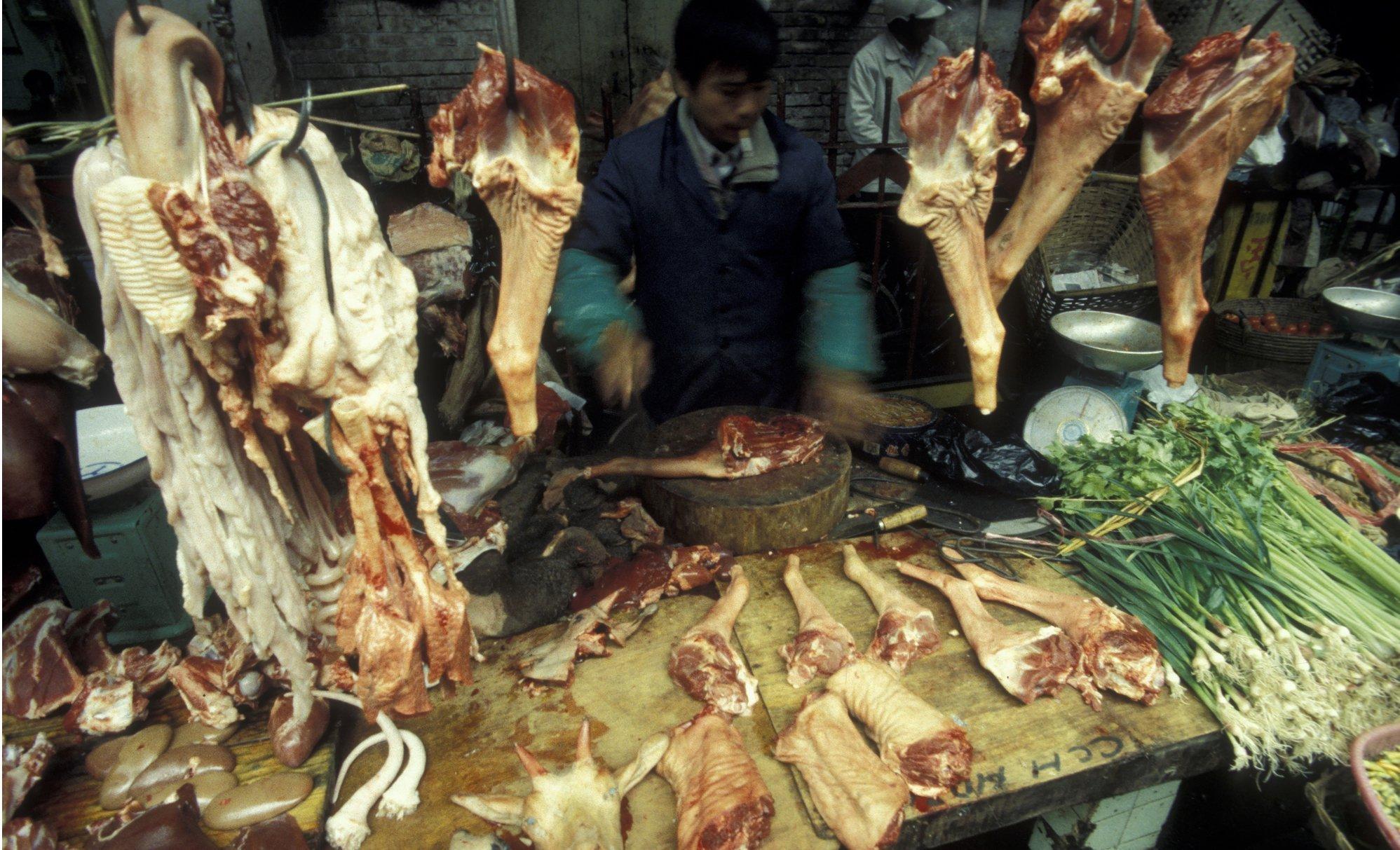 Ein Händler steht hinter seiner Theke auf dem  Fleischmarkt in der  Stadt Guangzhou. Vor ihm liegen viele Fleischstücke.