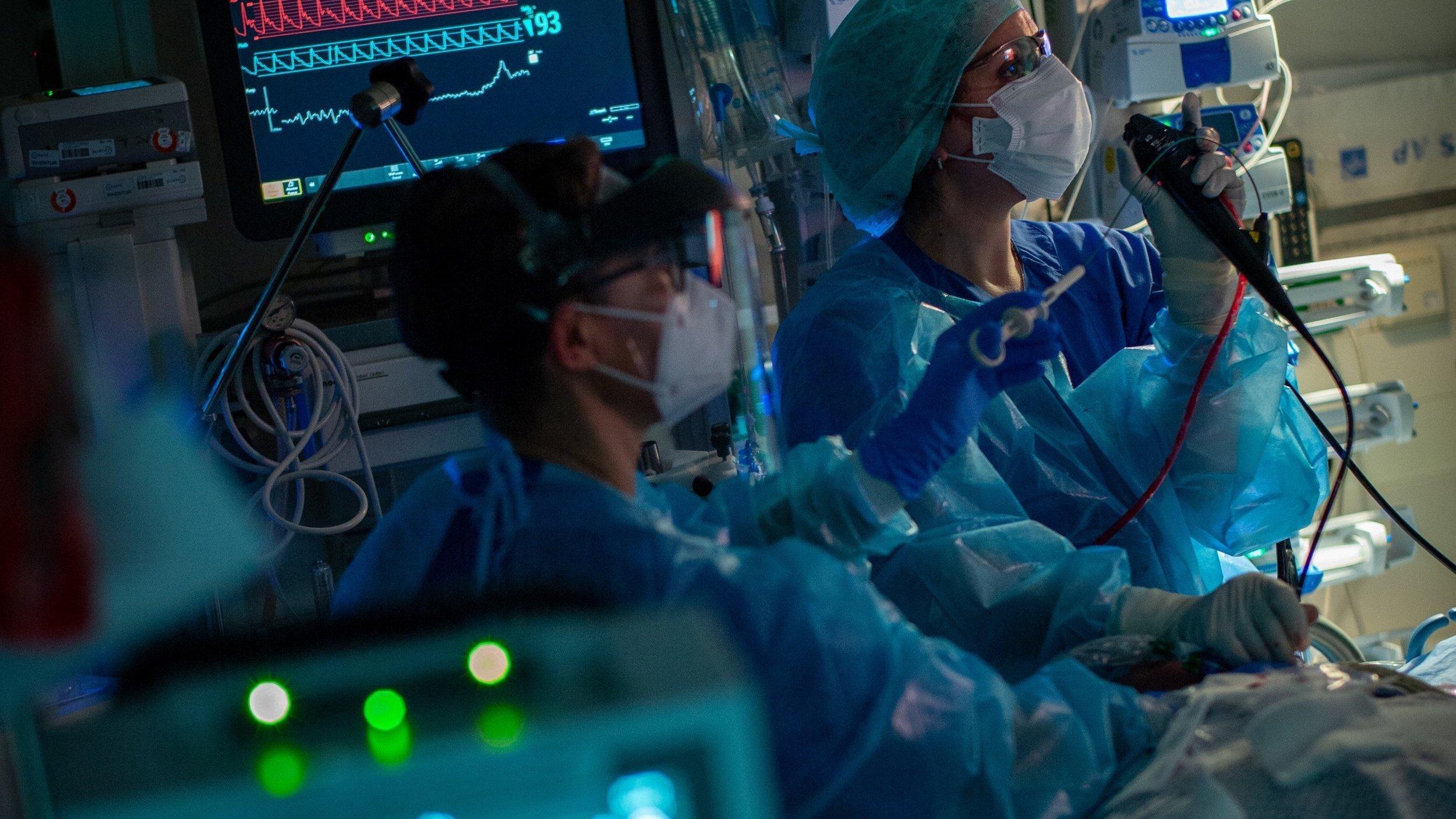 Intensivstation mit Bildschirmen. Zwei Mediziner in Schutzkleidung versorgen einen Covid-Patienten.