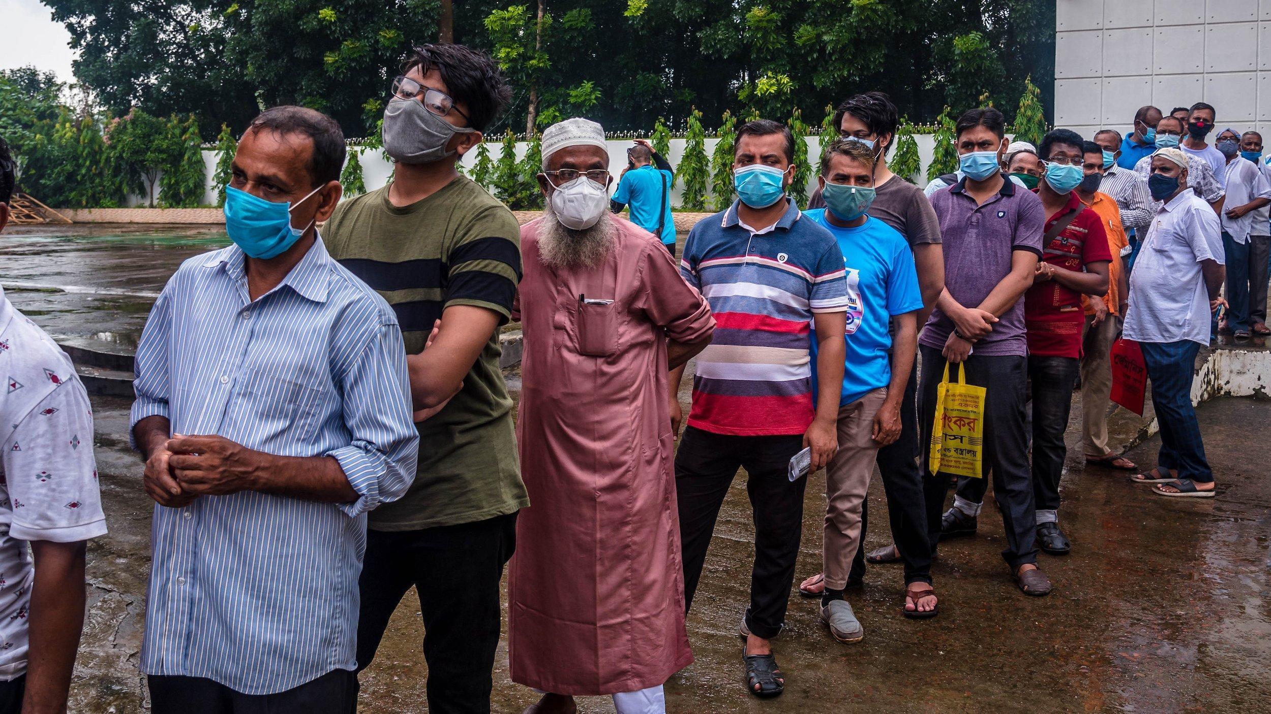 lange Schlange von Männern in einem Hinterhof vor dem Impfzentrum