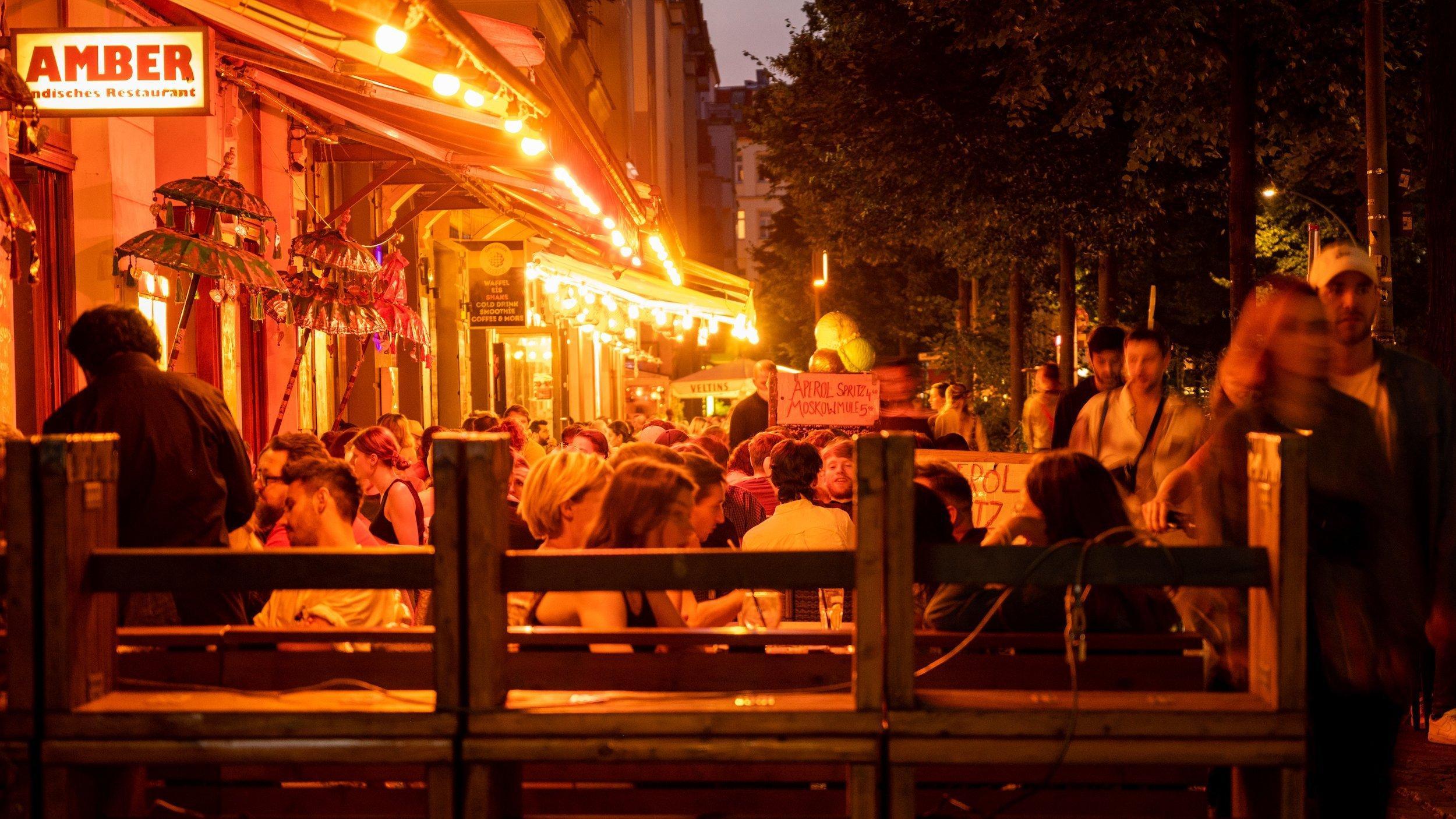 Menschen sitzen in Restaurants und Bars in Berlin-Friedrichshain.