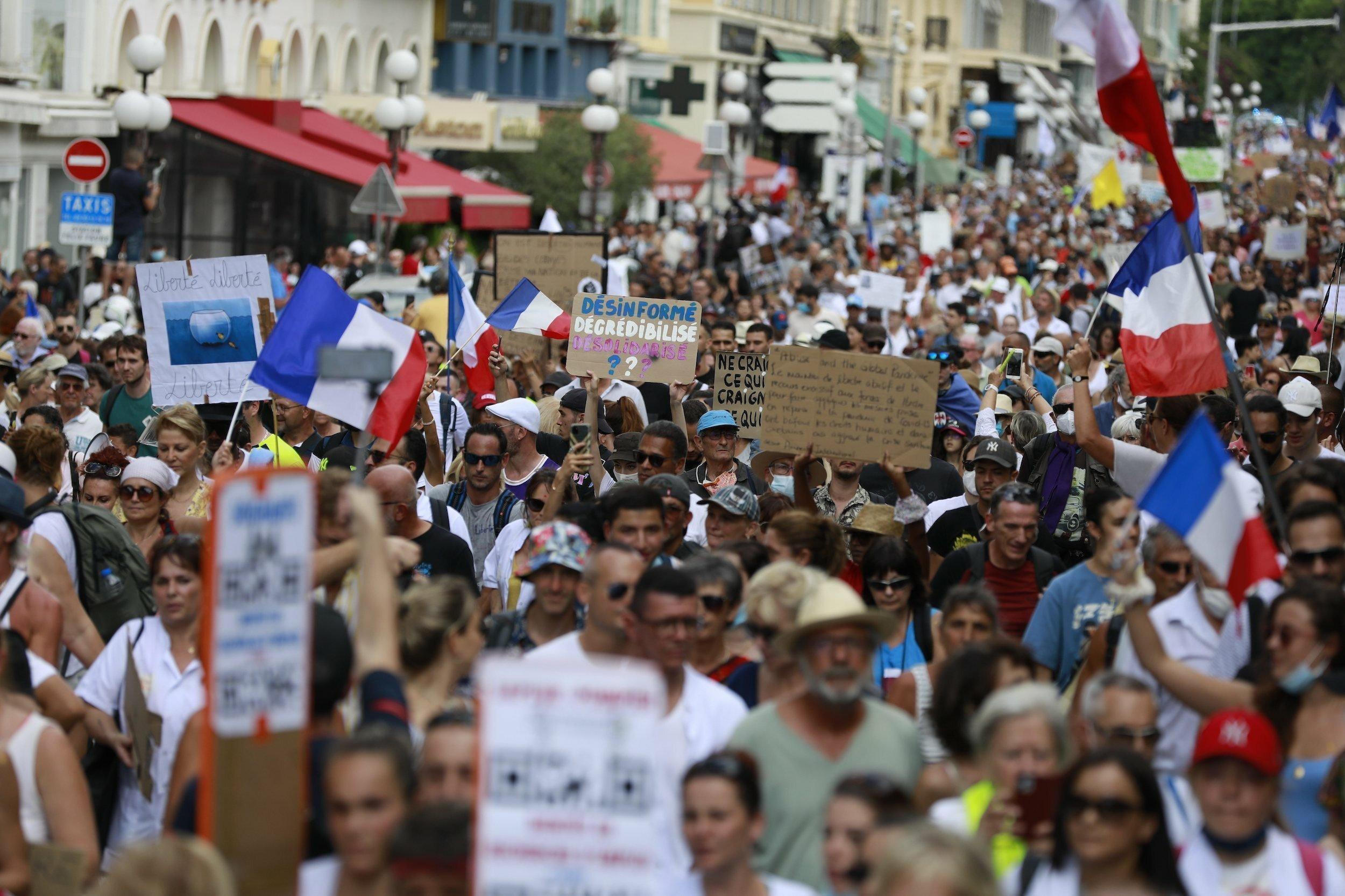Eine Menschenmenge weitgehend ohne Maske bewegt sich durch die Straße, mit vielen handgemalten Plakaten