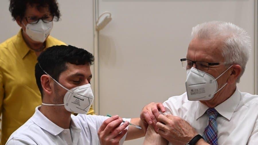 Der Politiker Kretschmann sitzt mit hochgekrempeltem Hemd auf einem Stuhl und bekommt von einem Arzt eine Impfung in den Oberarm gespritzt. Im Hintergrund steht seine Frau Gerlinde Kretschmann. An der Wand ist zu lesen: Zentrales Impfzentrum Klinikum Stuttgart