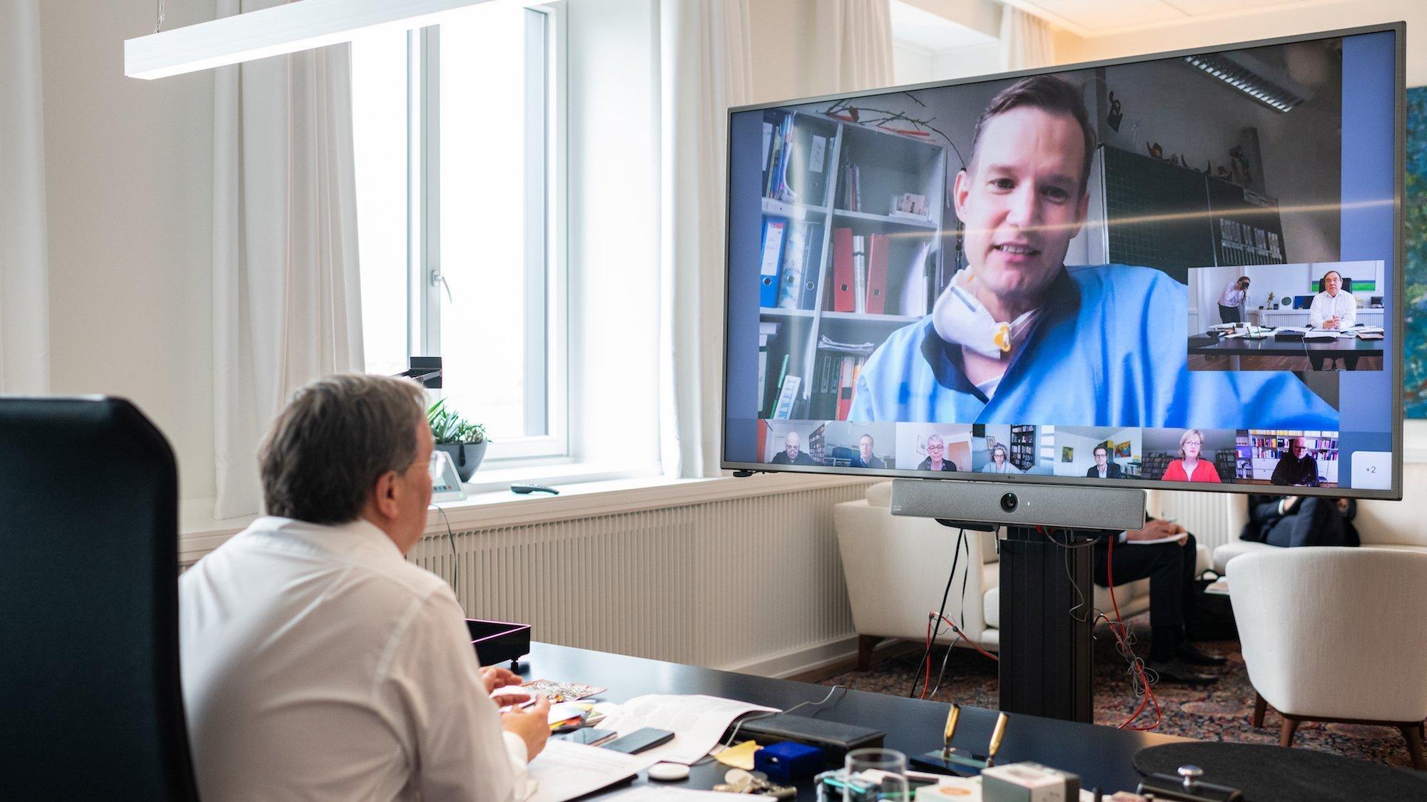 Das Bild zeigt den Ministerpräsidenten in seinem Büro. Er sitzt am Schreibtisch. Vor ihm ein großer Bildschirm, auf dem der Forscher Streeck zu sehen ist.