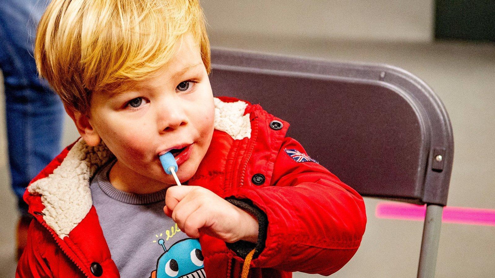 Ein kleiner Junge lutscht auf einem Plastikstäbchen mit Schaumstoffhülle herum.