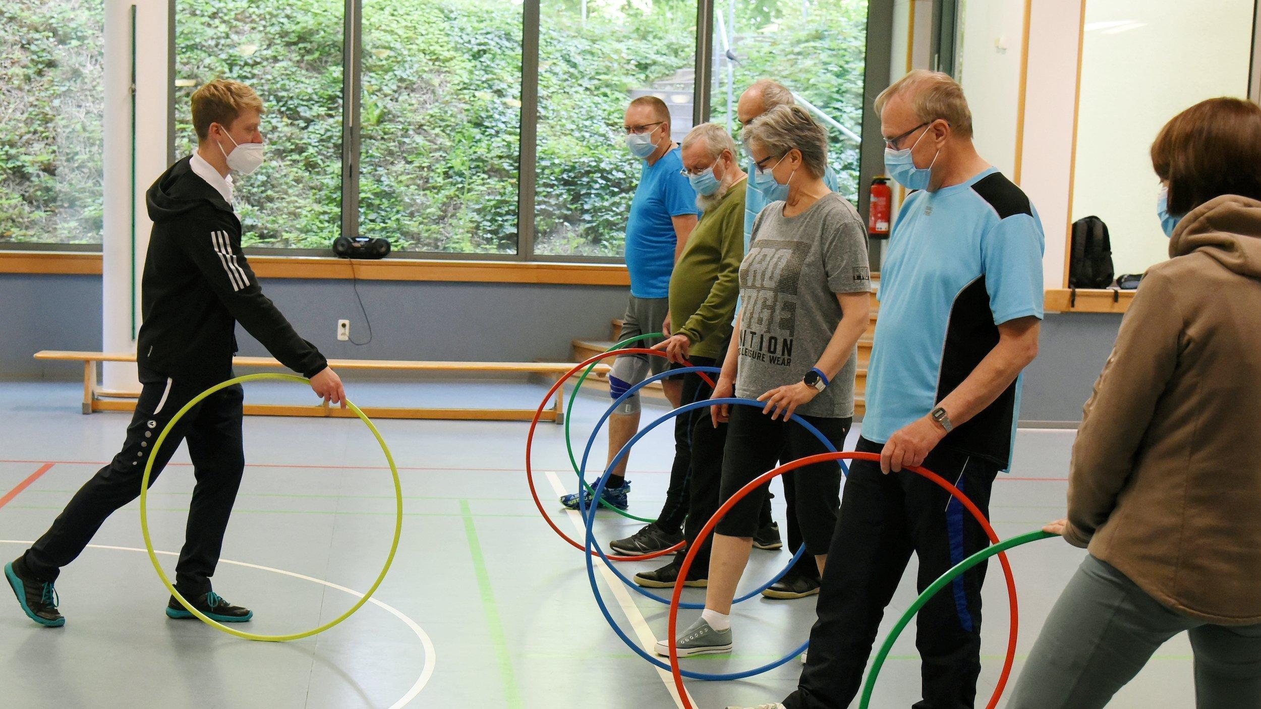 Reha-Therapie, der Trainer zeigt einer Gruppe mittelalter Menschen Bewegungsabläufe mit einem Gymnastikreifen
