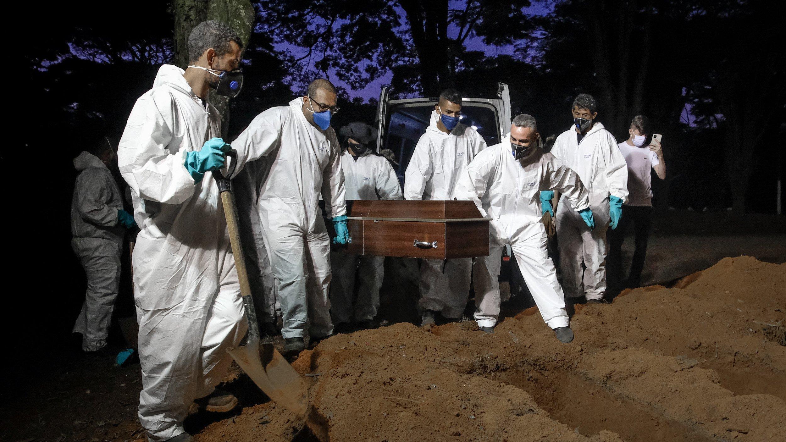 Menschen in weißer Schutzkleidung und mit Gesichtsmasken hieven bei nächtlichem Licht einen Sarg aus einem Beerdigungsfahrzeug und tragen ihn zum frisch ausgehobenen Grab.