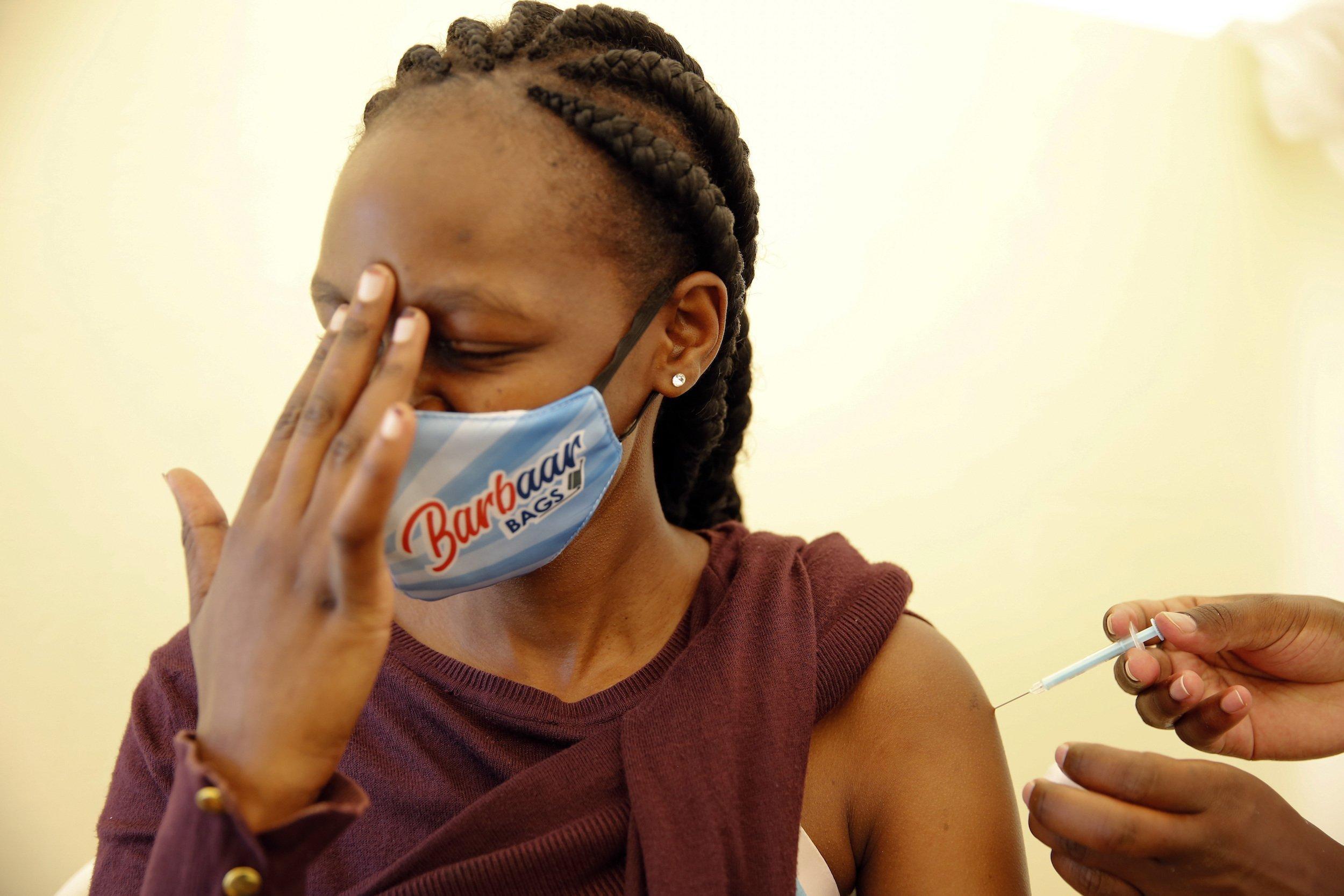 Die junge schwarze Frau hält sich die Finger ihrer rechten Hand an die Stirn, während sie die Impfspritze in den linken Oberarm bekommt.