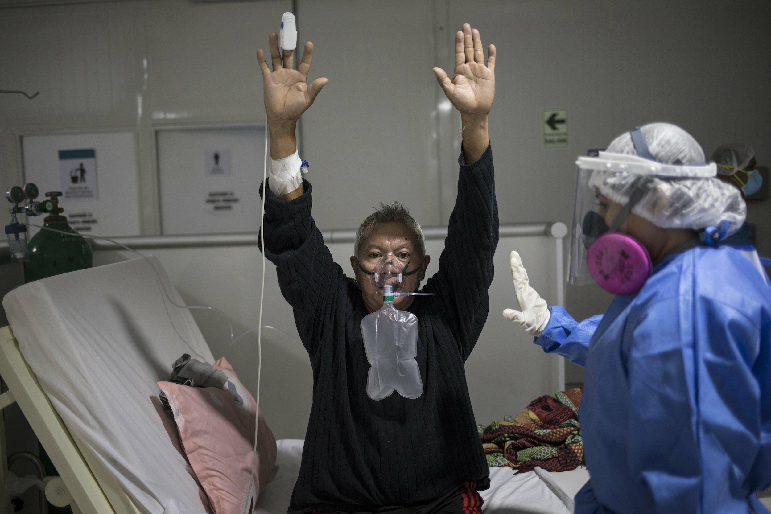 Ein älterer Mann sitzt mit nach oben ausgestreckten Armen in seinem Krankenbett. Er hat einen Sauerstoffbeutel über dem Gesicht und ein Sauerstoff-Messgerät an seinem Finger. Neben ihm steht eine medizinische Fachkraft, die mit ihm spricht.