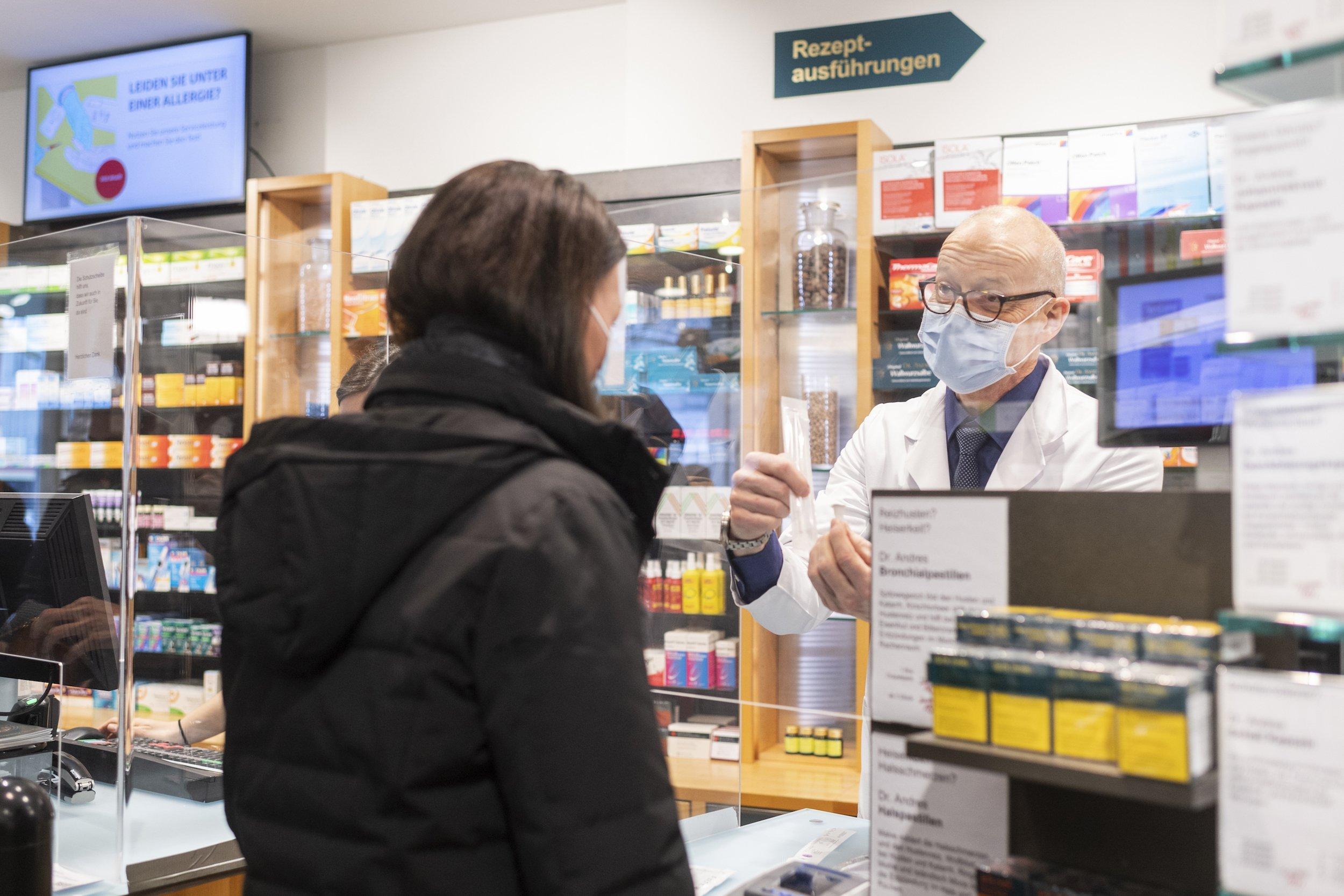 Der Apotheker hält hinter einer Schutzscheibe einen Beutel mit den Komponenten des Schnelltests in die Höhe und zeigt sie der Kundin.