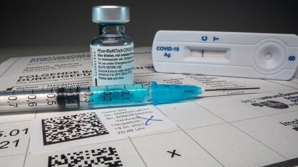 Eine Ampulle Corona-Impfstoff, eine Spritze, ein Schnelltest und ein medizinisches Formular