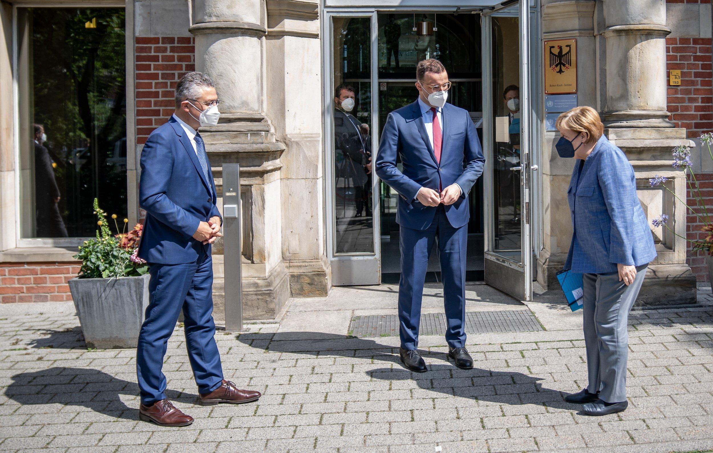 Bundeskanzlerin Angela Merkel wird neben Jens Spahn von Lothar Wieler, Präsident des Robert Koch Instituts (RKI), vor dem Eingang des RKI begrüsst.