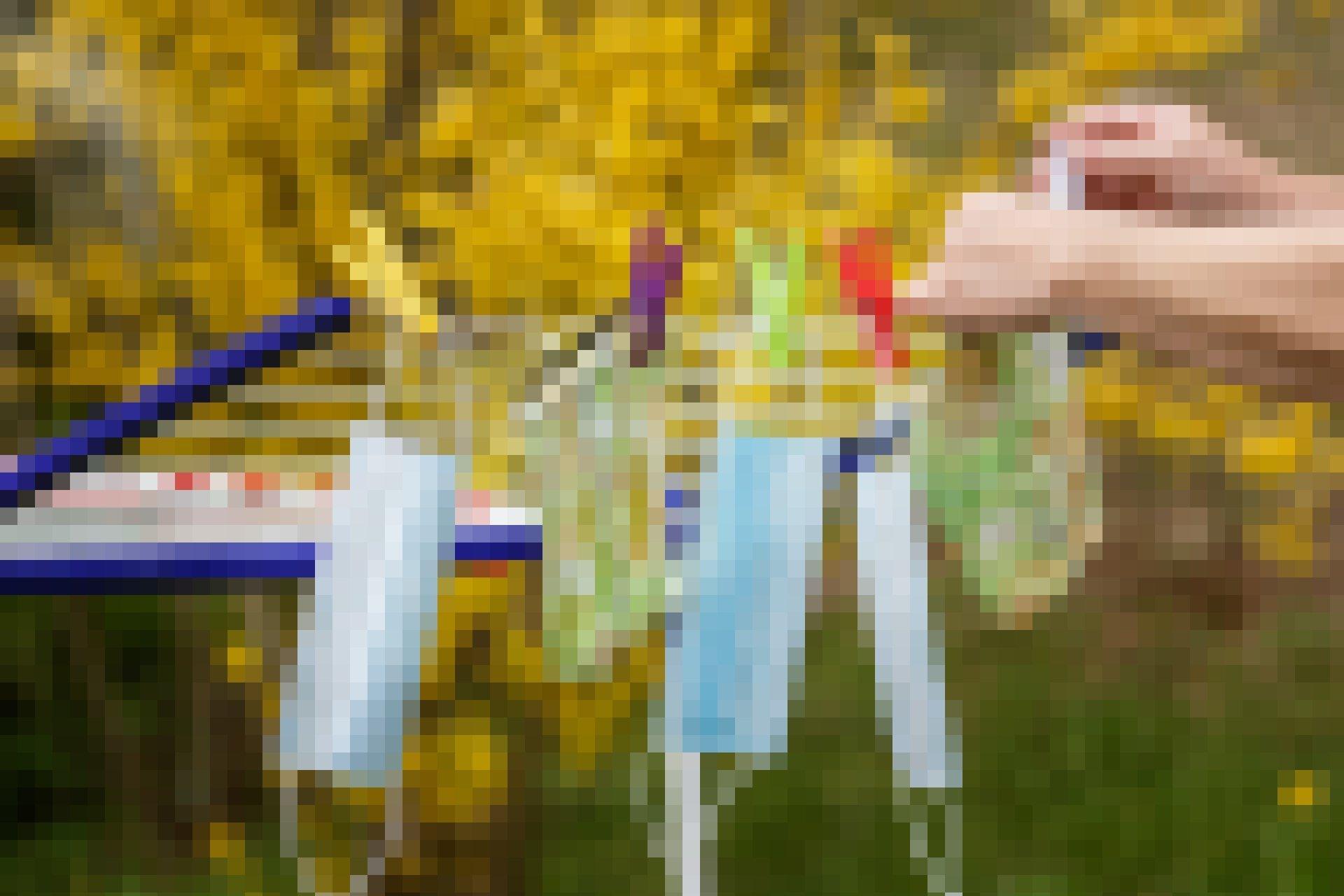 Ein Wäschständer, der draußen steht, mit Wäscheklammern und einigen zum Trocknen aufgehängten Mund-Nase-Schutz, Masken.