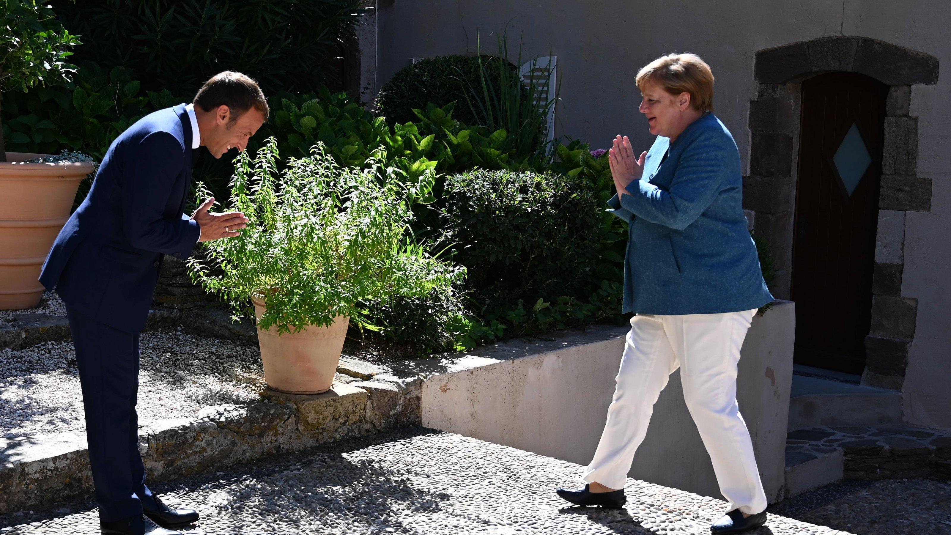 Das Bild ist im Freien aufgenommen. Macron steht links und macht eine tiefe Verbeugung mit zusammengefalteten Händen. Merkel kommt von rechts und macht eine freundliche Geste, aber auch ein bisschen abwehrend, so als sei ihr die Ehrerbietung zu viel. Lassen wir also Macron vor dem Strauch verbeugen, der in der Mitte des Bildes steht. Passt ja auch zum Thema.