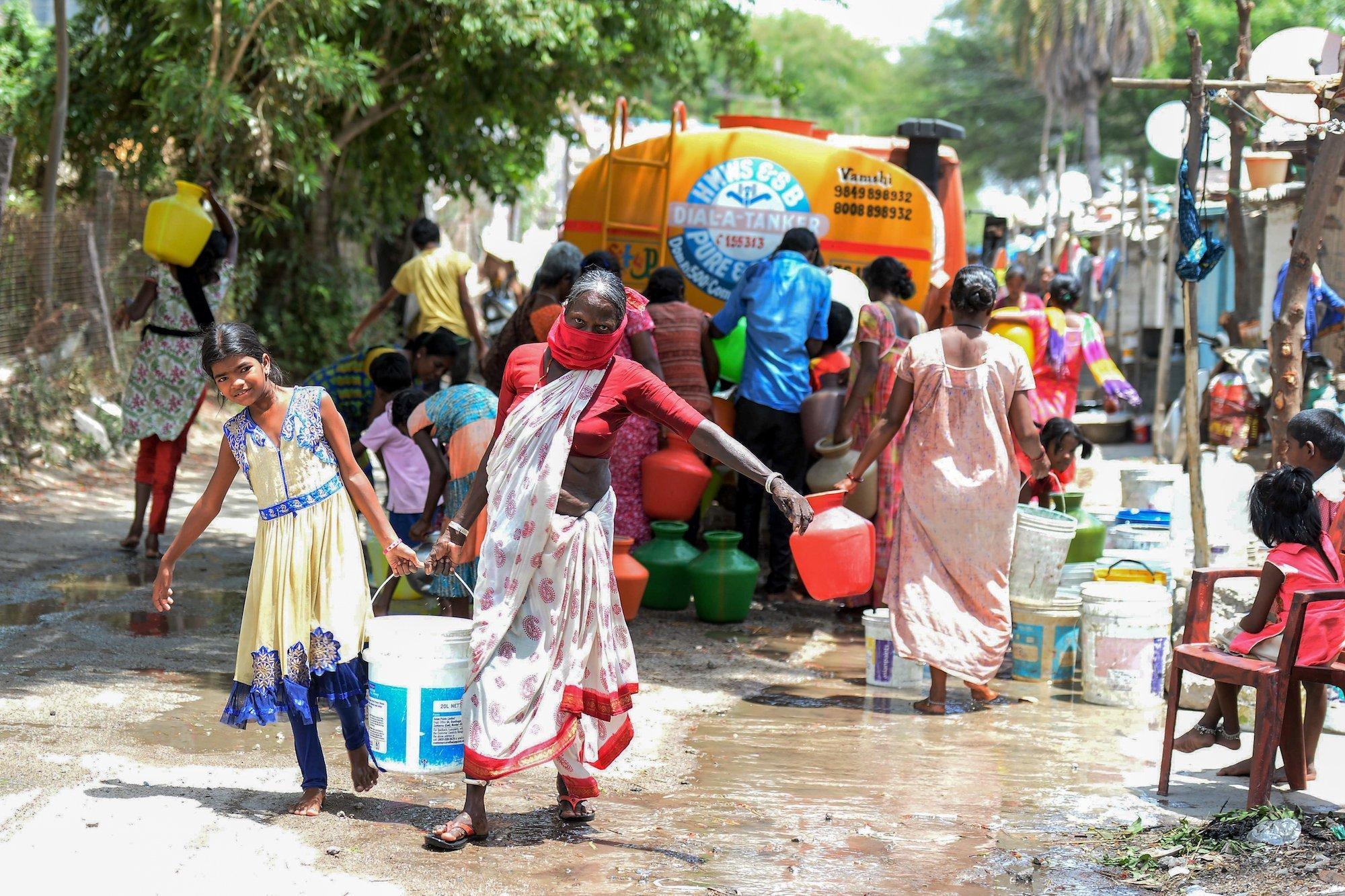 Die gezeigte Szene stammt aus dem Mai 2020. In einem Slum im indischen Secunderabad bringt ein Lastwagen kostenloses Trinkwasser. Viele Menschen stehen um den Lastwagen herum und versuchen, etwas abzubekommen. Eine Frau und ein Mädchen waren erfolgreich. Sie tragen einen großen Wasserbehälter nachhause.