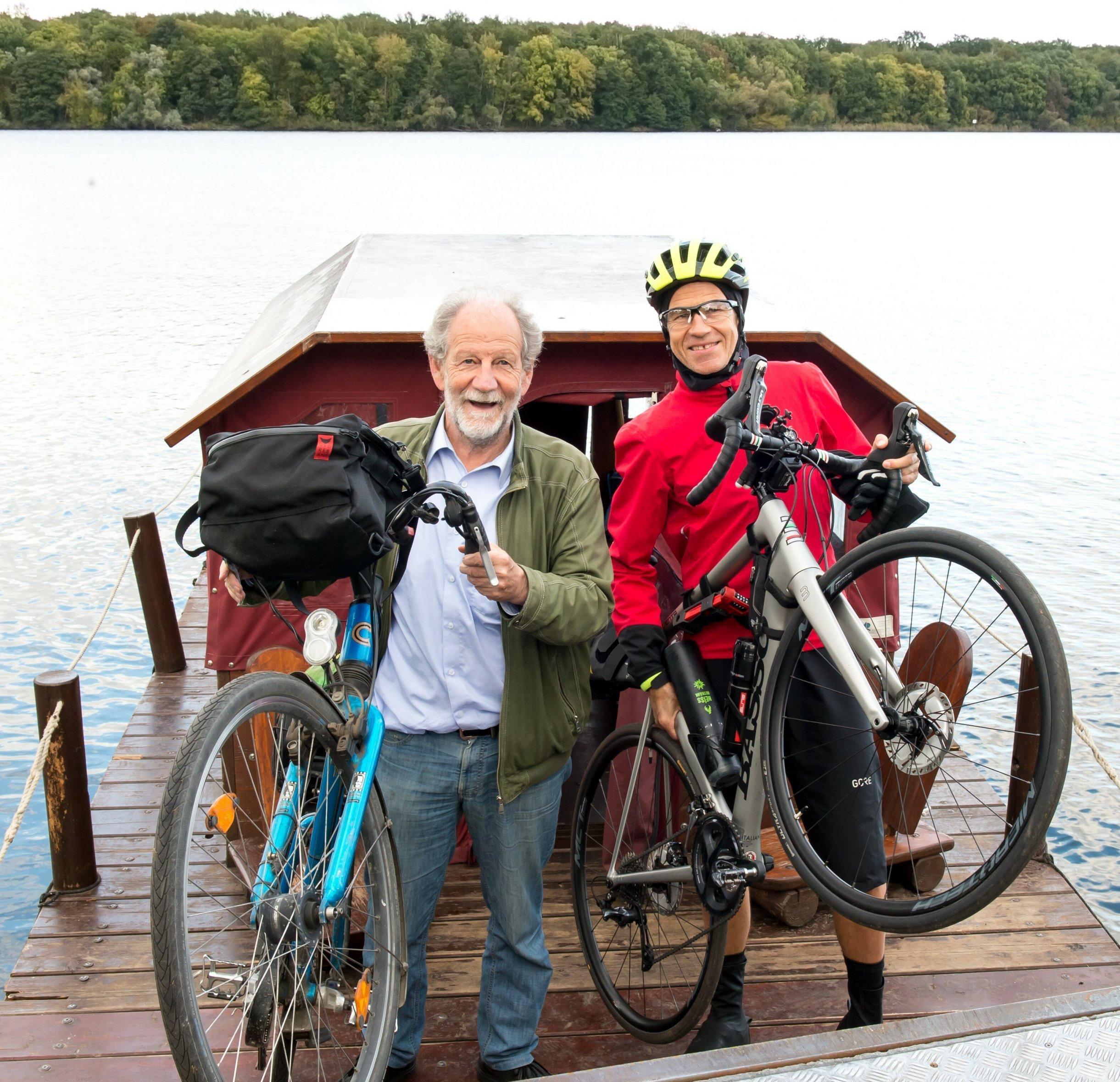 Michael Cramer und Martin C Roos lupfen nebeneinander lachend ihr Fahrrad am Bug des Wasservehikels; im Hintergrund der von der Havel gespeiste Jungfernsee.