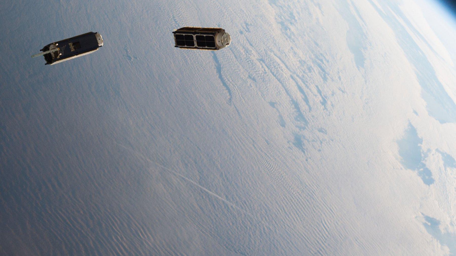 Zwei wie Schuhkartons geformte Satelliten driften um die blaue Erde
