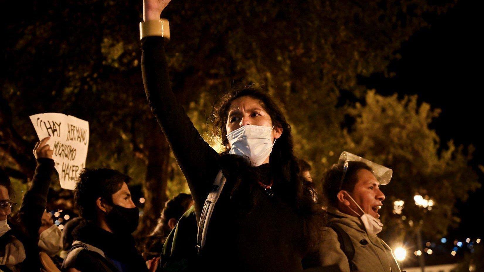 Junge schwarzgekleidete Frau mit weißem Mundschutz hält Hand kämpferisch in die Höhe. Es ist Nacht. Im Hintergrund Bäume, Laternen und weitere Demonstrierende.