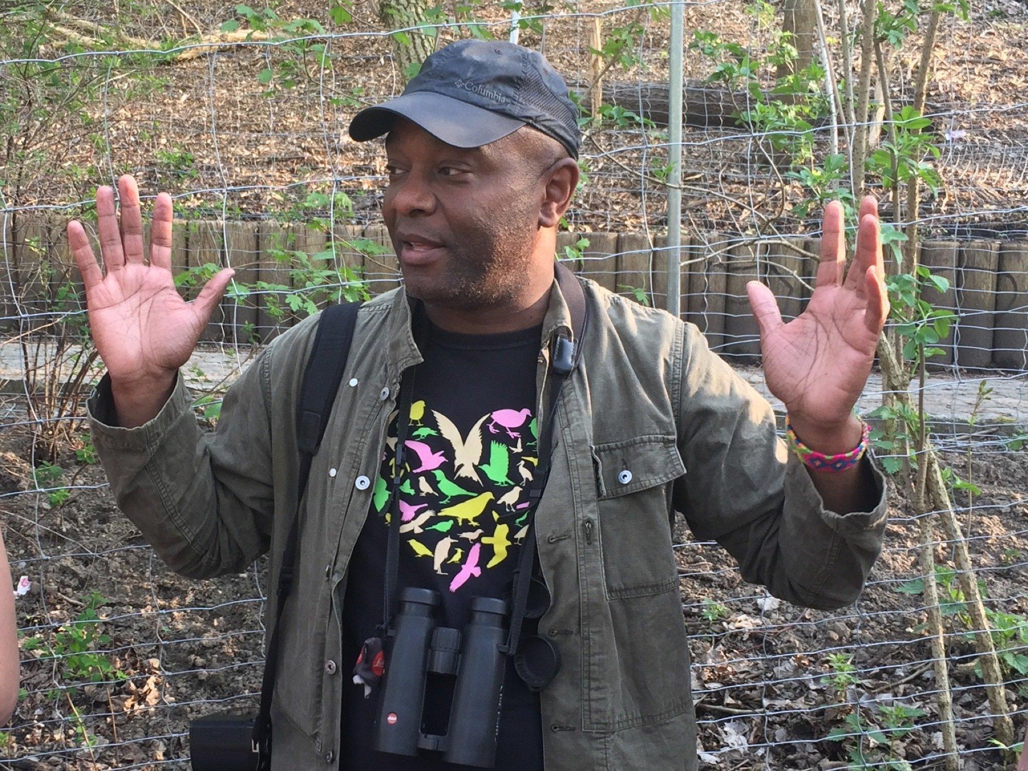 Dargestellt ist der schwarze Vogelexperte David Lindo mit ausgebreiteten Armen und einem Fernglas um den Hals.