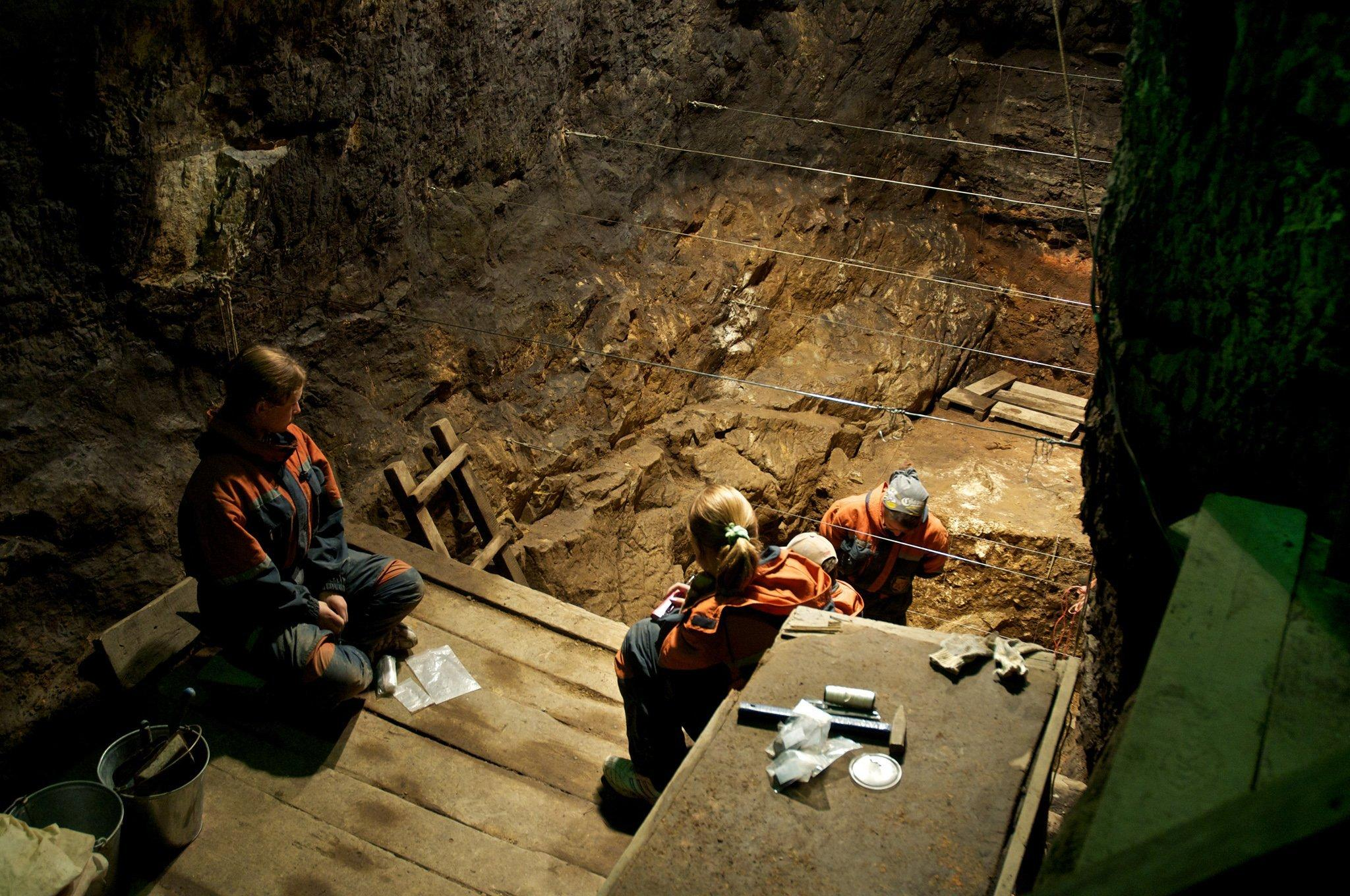 Gezeigt wird ein Blick auf die gelblichen Erdschichten innerhalb der Denisova-Höhle in Sibirien. Dort am Boden sind zu Paläoanthropologen zu sehen, die nach menschlichen Fossilien graben. Im Jahr 2008finden sie unscheinbare, mindestens 30.000Jahre alte Knochenreste. Doch die spätere Analyse der Erbsubstanz eines Stücks Fingerknochens ergibt eine Sensation: Die DNA unterscheidet sich so sehr sowohl vom Homo sapiens als auch vom Neandertaler, dass es sich bei dem Fossil um die Relikte einer bislang unbekannten Menschenform handeln muss. Die Forscher haben den Denisova-Menschen entdeckt.