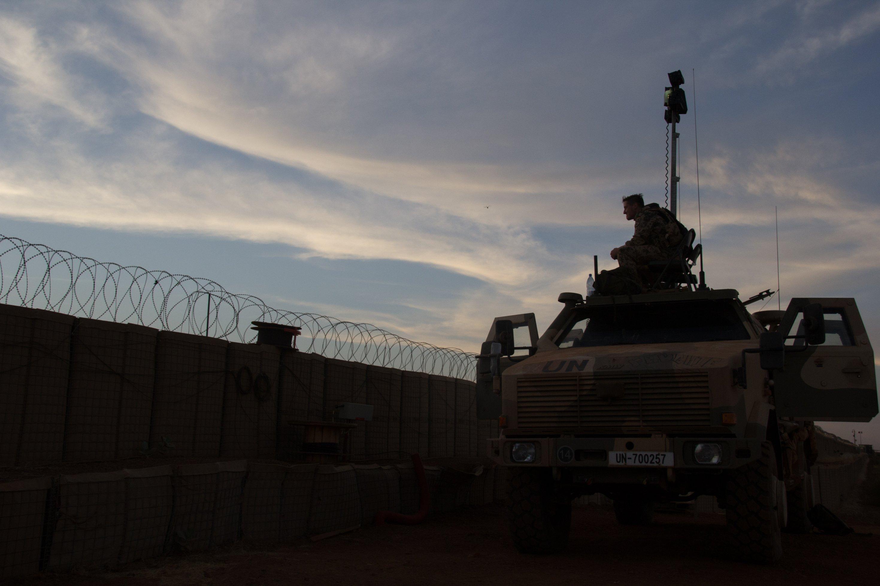 In der Abenddämmerung sind die Umrisse eines Panzers und von Soldaten zu sehen, die am neben einem Zaun – dem Umgrenzungszaun des Feldlagers – auf Ausguck sind.