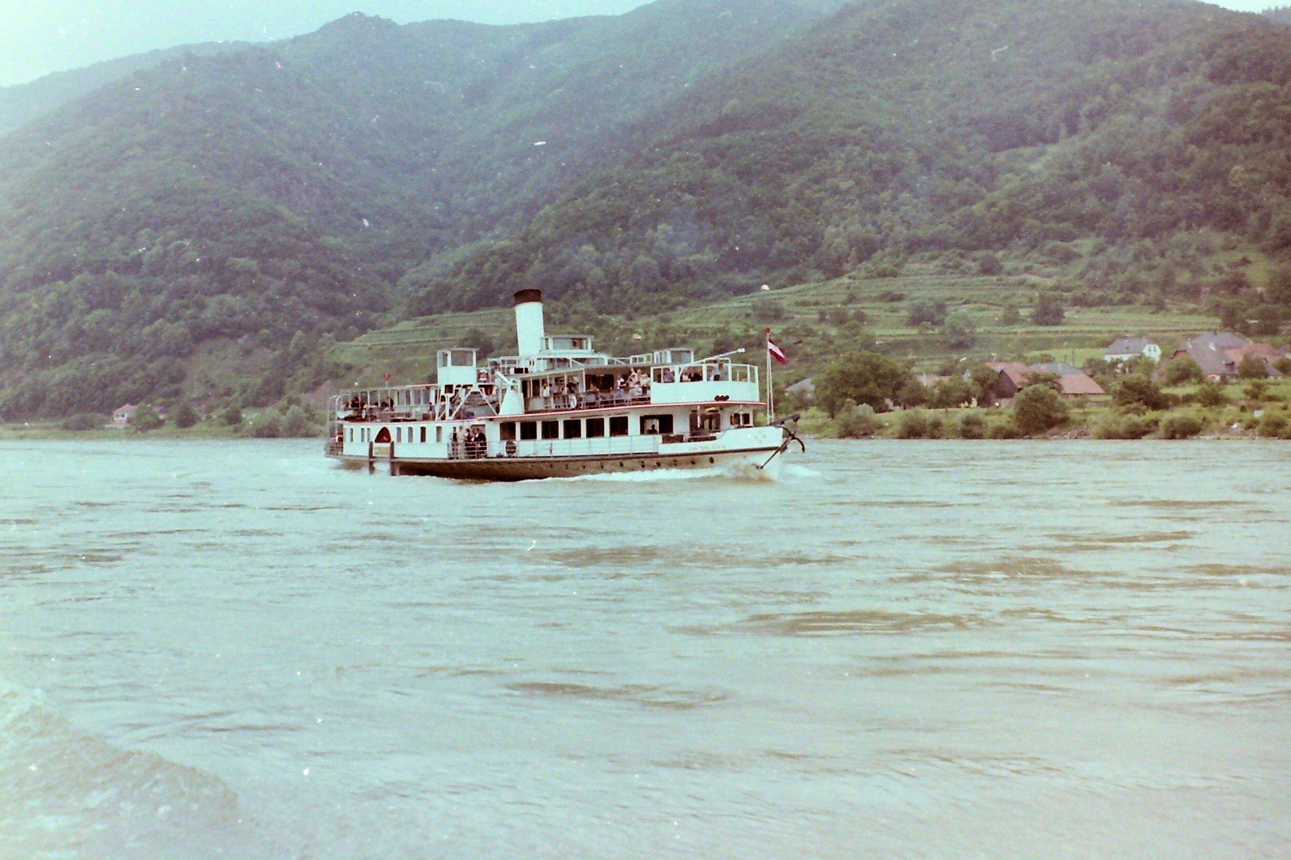 Ein kleines Dampfschiff fährt auf dem Fluss