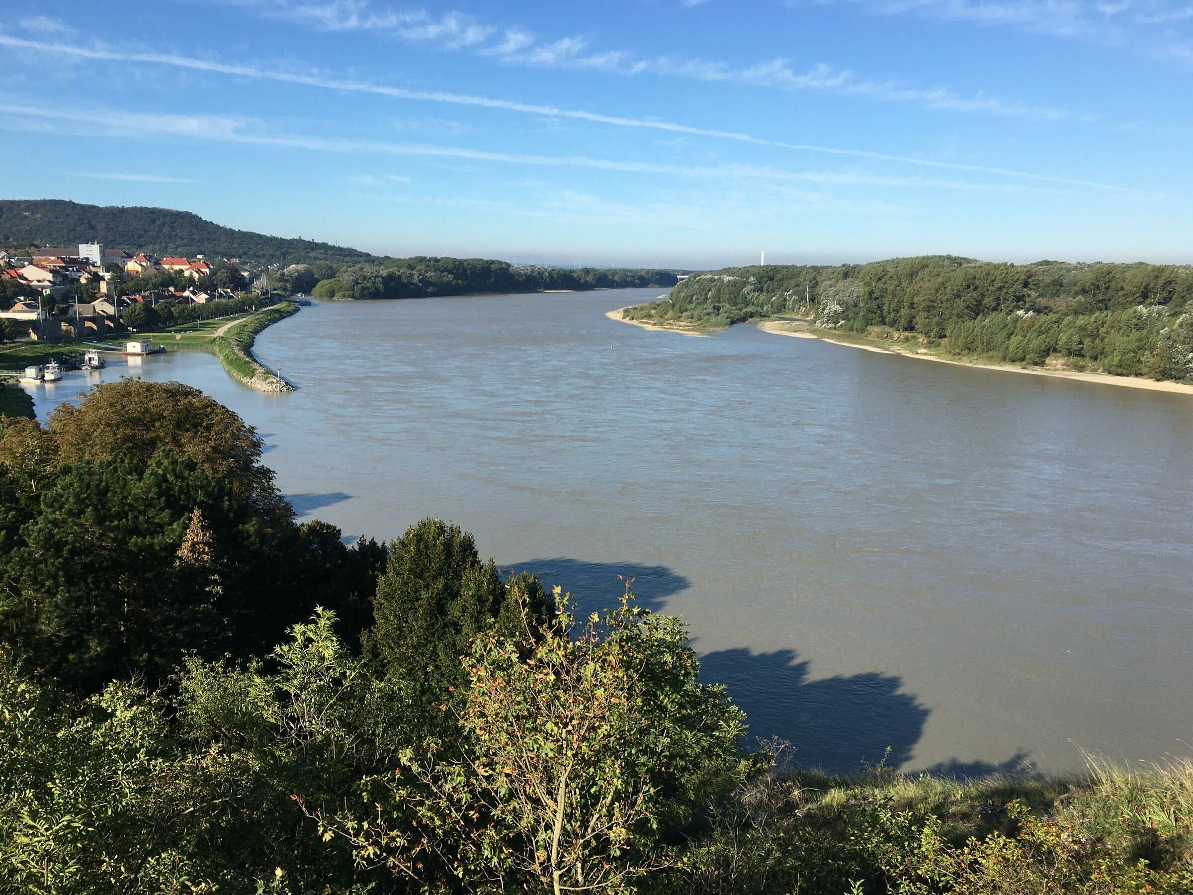Fluss mit Umland, flussaufwärts blickend, links ein paar Häuser einer historischen Stadt.