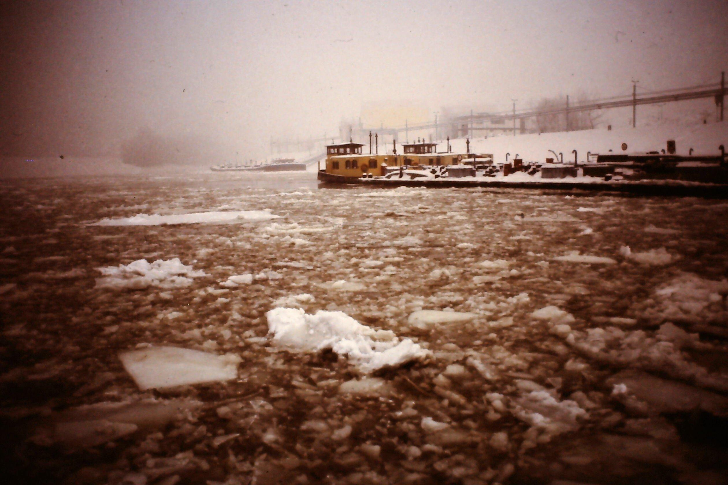 Frachtschiff im Hafen, auf dem Fluss treiben Eisschollen