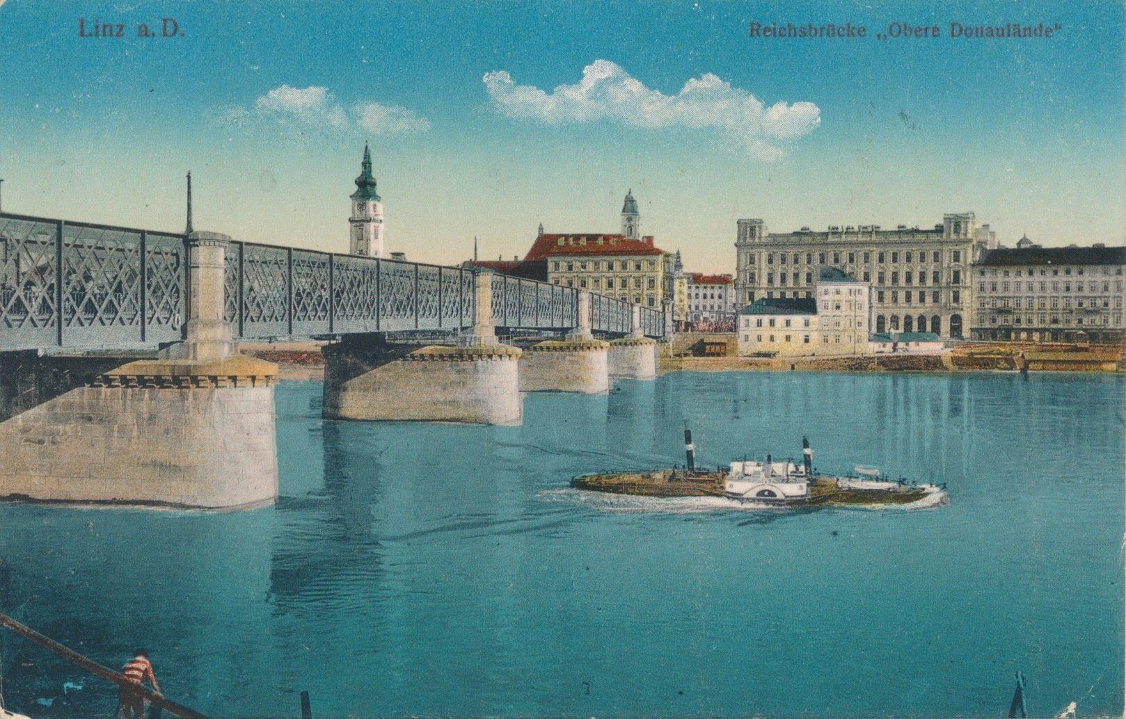 Brücke, Häuser, türkisblauer Fluss und Schiff.