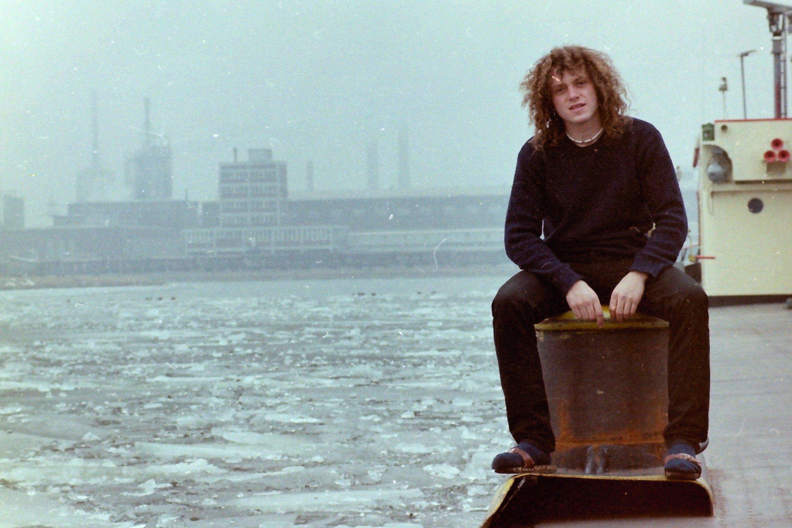 Junger Mann mit langen lockigen Haaren am Hafen