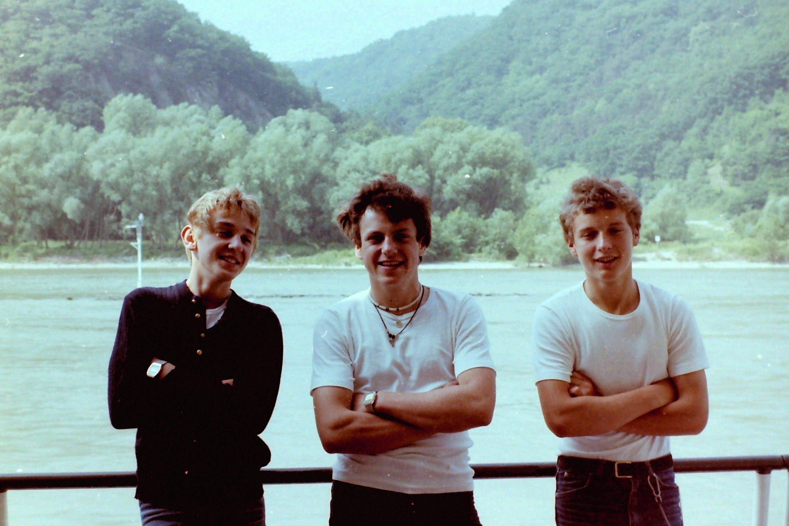 Drei junge Männer in Matrosenkleidung auf einem Schiff.