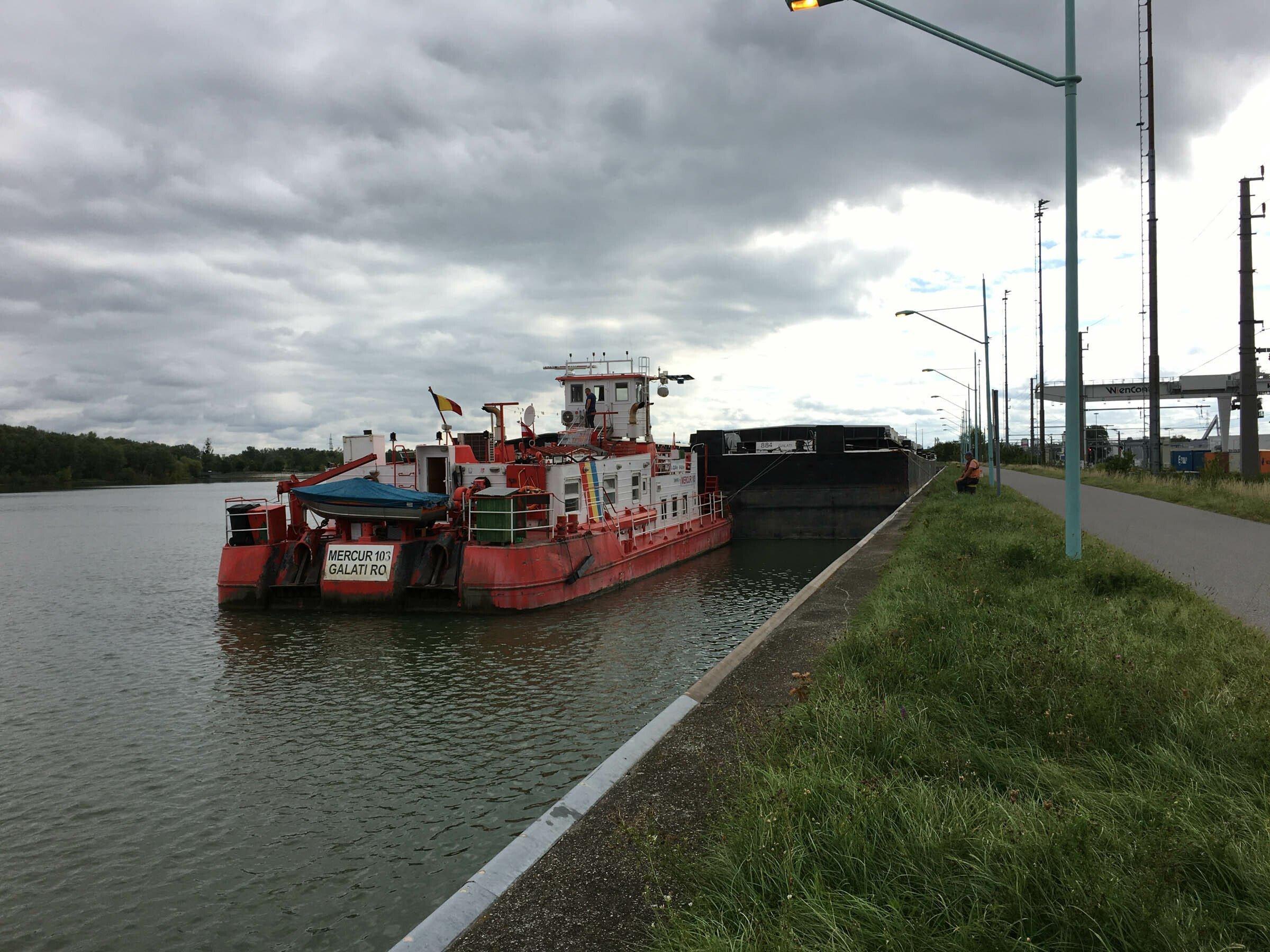 Kleines rotes Frachtschiff steht am Ufer des Flusses.