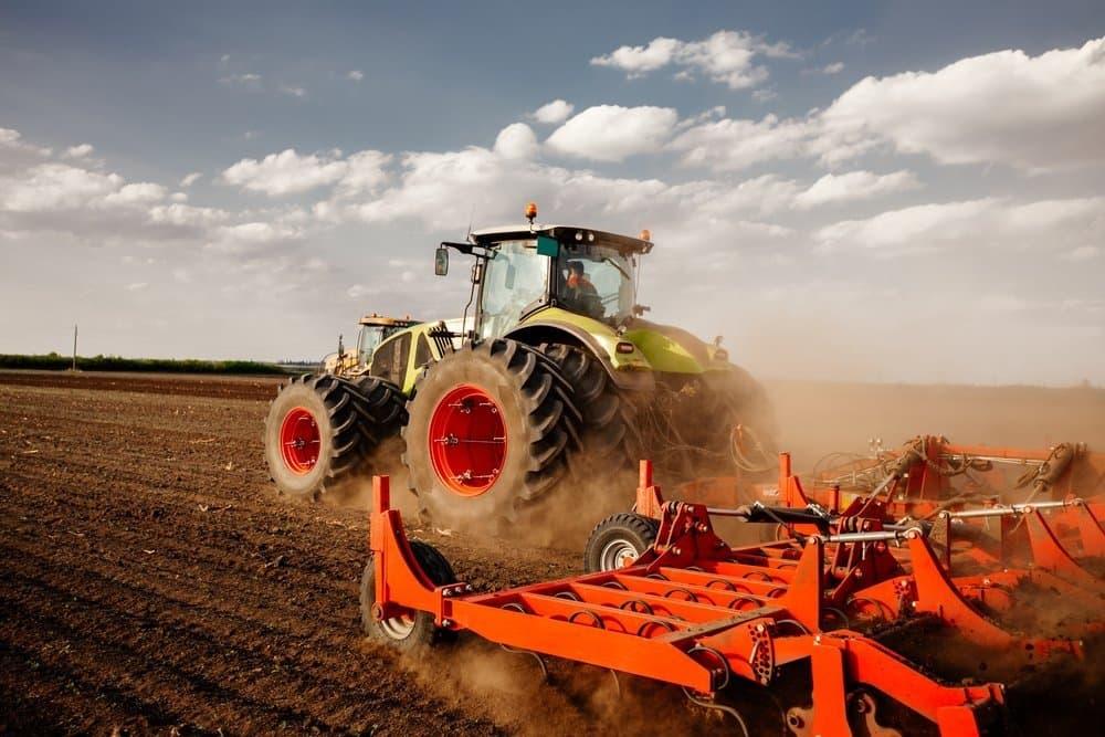 Ein Traktor zieht auf einem leeren Feld eine rote Landmaschine hinter sich her.