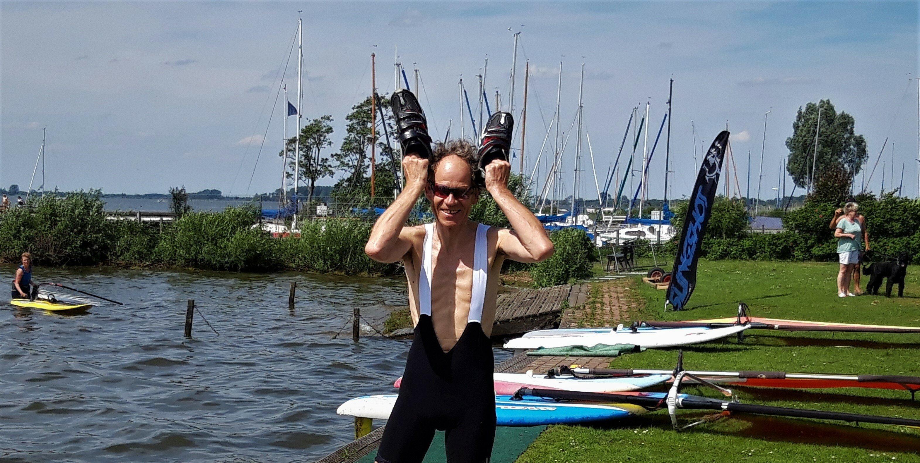 Autor Martin C posiert mit den Radschuhen in der Hand am vom Wind aufgewühlten Wasser des Sees.