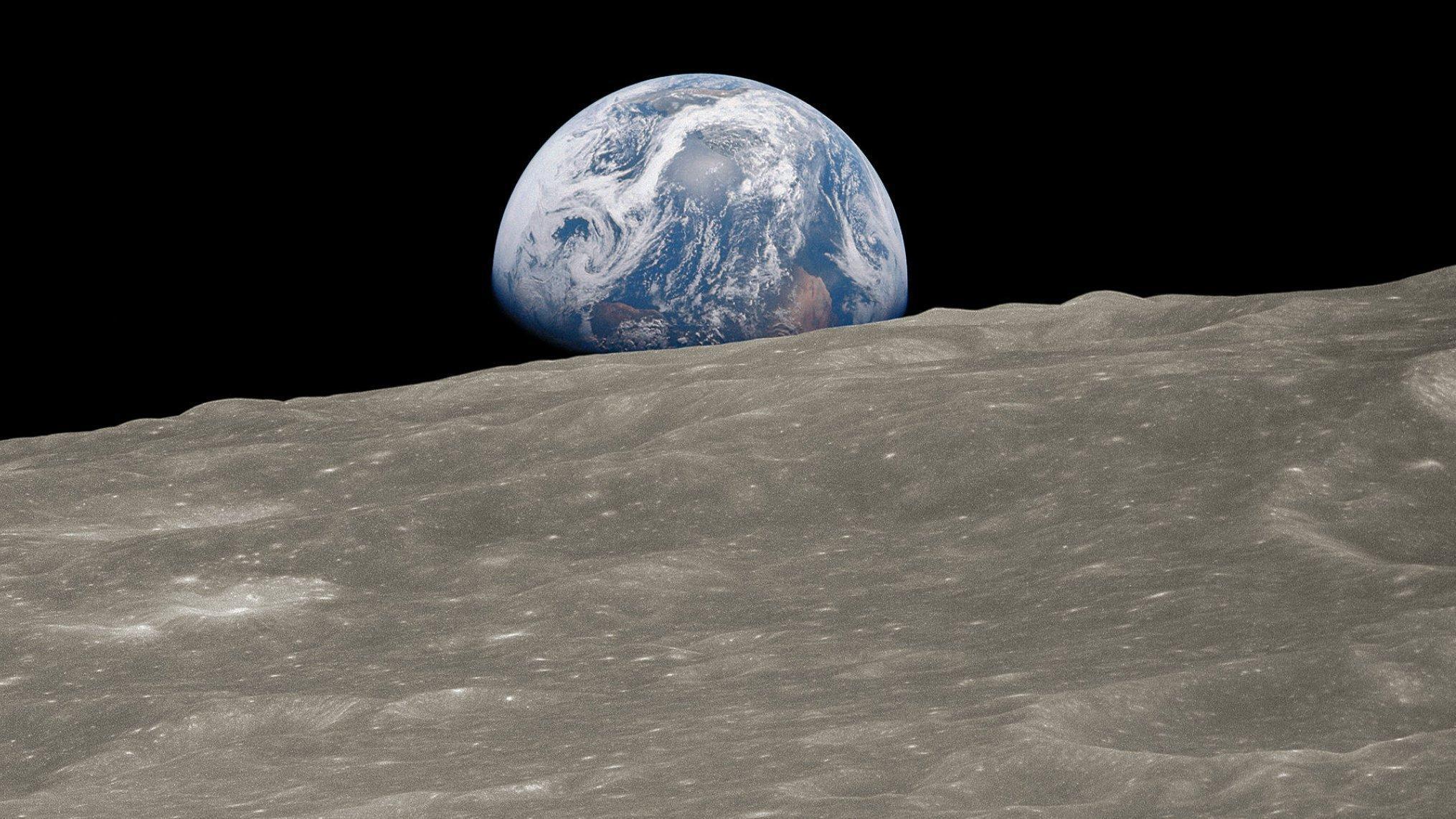 Foto der Mondoberfläche mit Tälern, Bergen und Kratern, darüber die Erde, die sehr plastisch wirkt