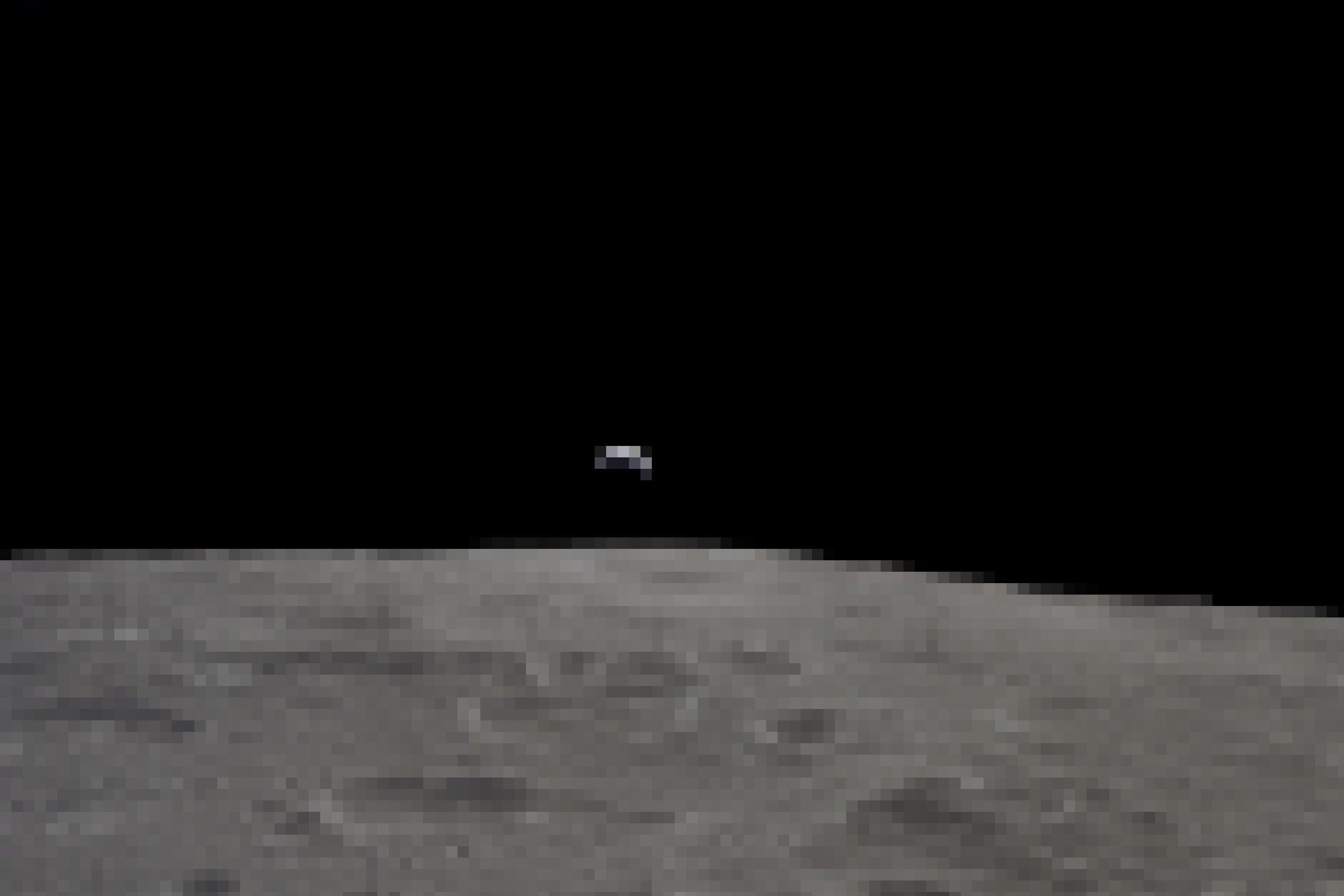 Die graue Oberfläche des Mondes und darüber eine sehr sehr feine Erdsichel, mit dem überwältigendem Schwarz des Weltalls darüber. Das Bild am 19. November 1969von der Crew von Apollo 12aus dem Mondorbit aufgenommen.