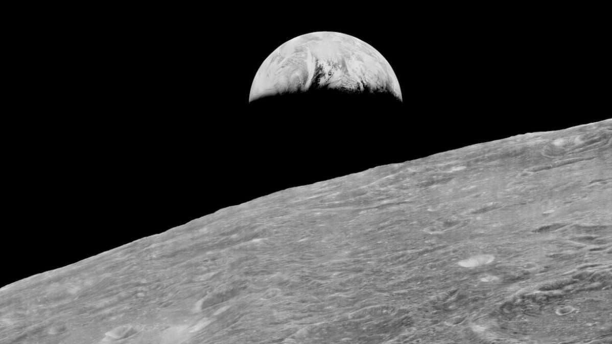 Schwarzweiß-Foto: Die angeschnittene Mondoberfläche, darüber die Erde mit gut erkennbaren Wolkenbändern. Es ist das erste Earth rise-Bild, aufgenommen vom Lunar Orbiter 1der NASA im August 1966.