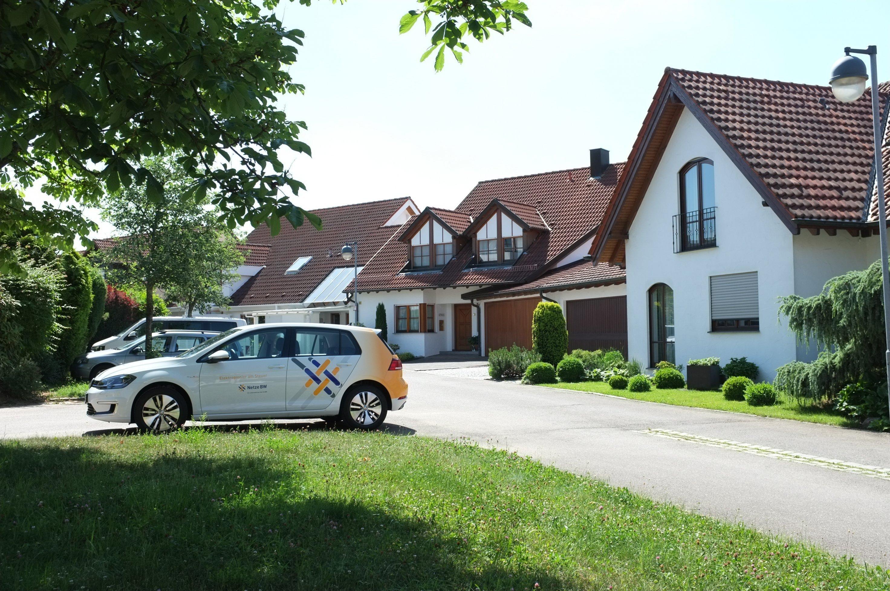 Straße mit Einfamilienhäusern uns E-Autos.
