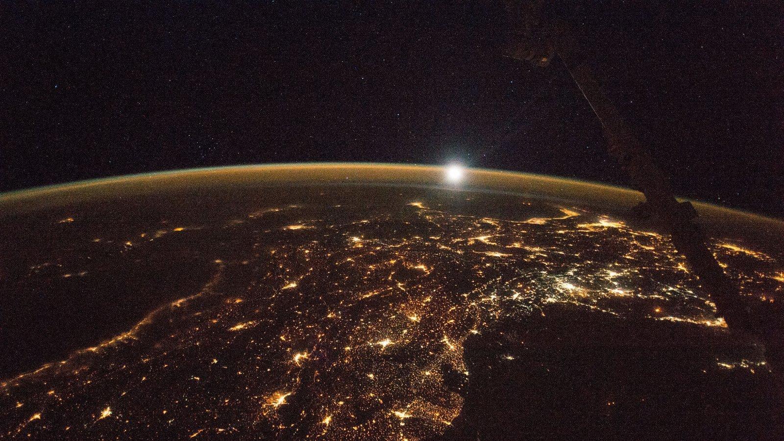 Die Erde bei Nacht, aufgenommen von der Internationalen Raumstation, mit vielen leuchtenden Städten, rechts im Bild ist ein dunkler Ausleger der Raumstation.