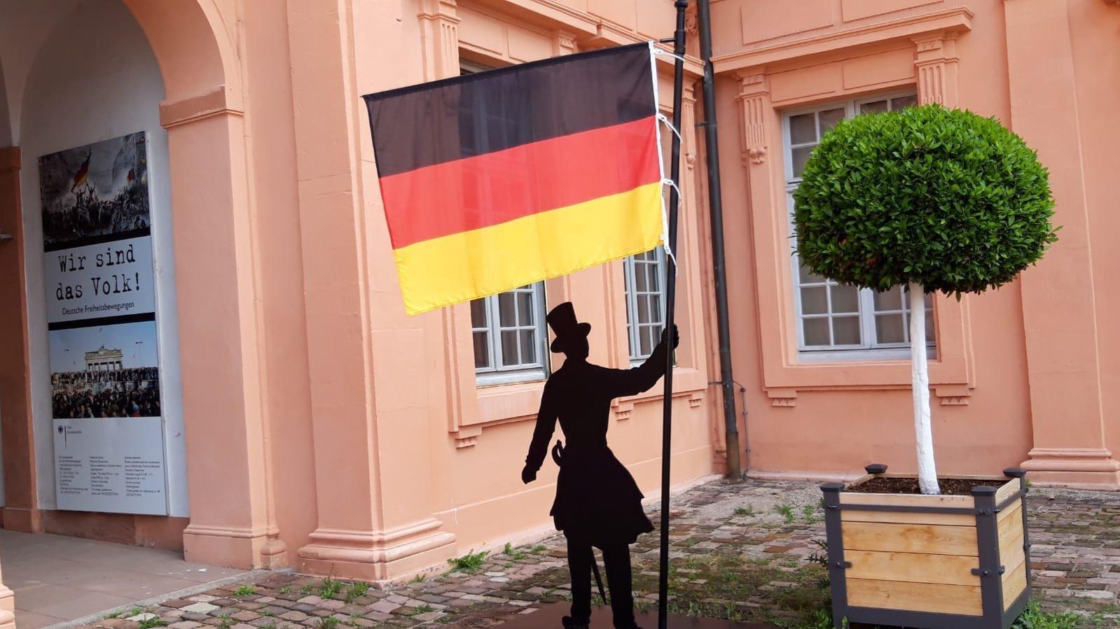 Ein Museums-Hinweis-Männchen mit Deutschlandflagge vor dem rostroten Sansteingebäude.
