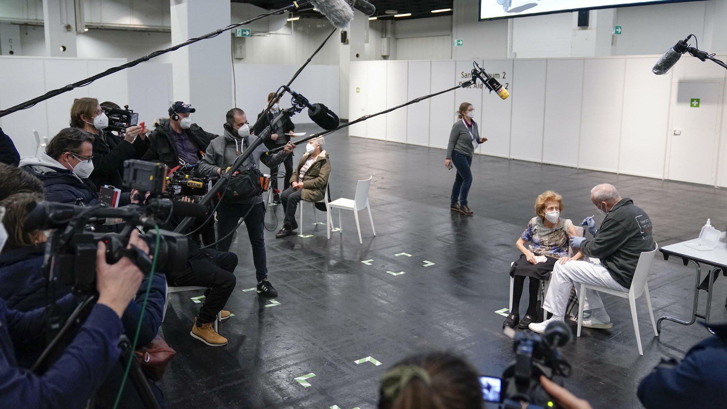 In einer großen Halle: Menschen mit Kameras und Mikrofonen umringen eine ältere Frau auf einem Stuhl, die sich von einem Mann eine Spritze in den rechten Oberarm verabreichen lässt.