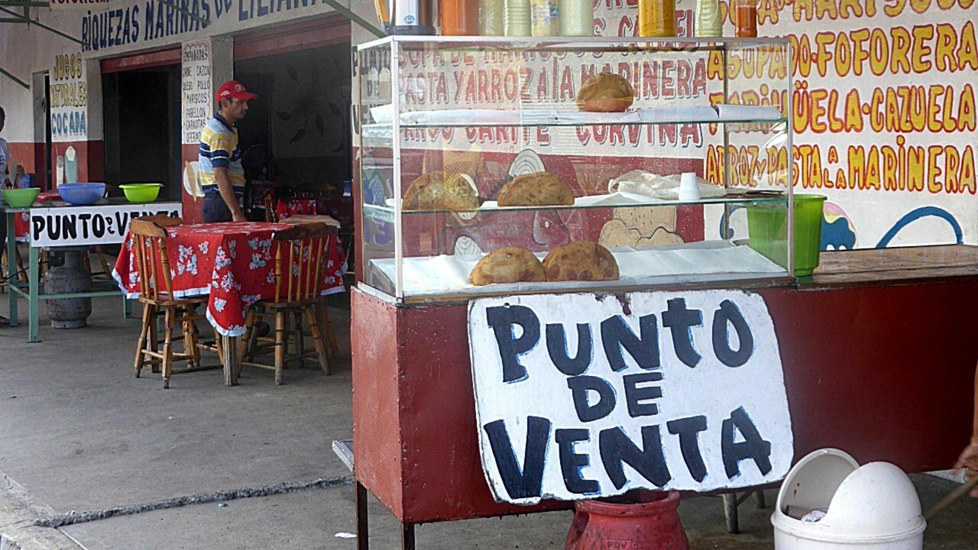 """Das Foto zeigt den Straßenbereich eines sehr einfachen Lokals in Venezuela. Im Zentrum ist eine Vitrine zu sehen mit der Aufschrift """"Verkaufsstand"""" (punto de venta). Darin liegen sehr spärlich verteilte frittierte Teigtaschen. Darauf steht ein Arsenal an Saucen."""